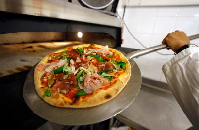A student puts a pizza in an oven in a pizza school during a course in Cap d'Ail
