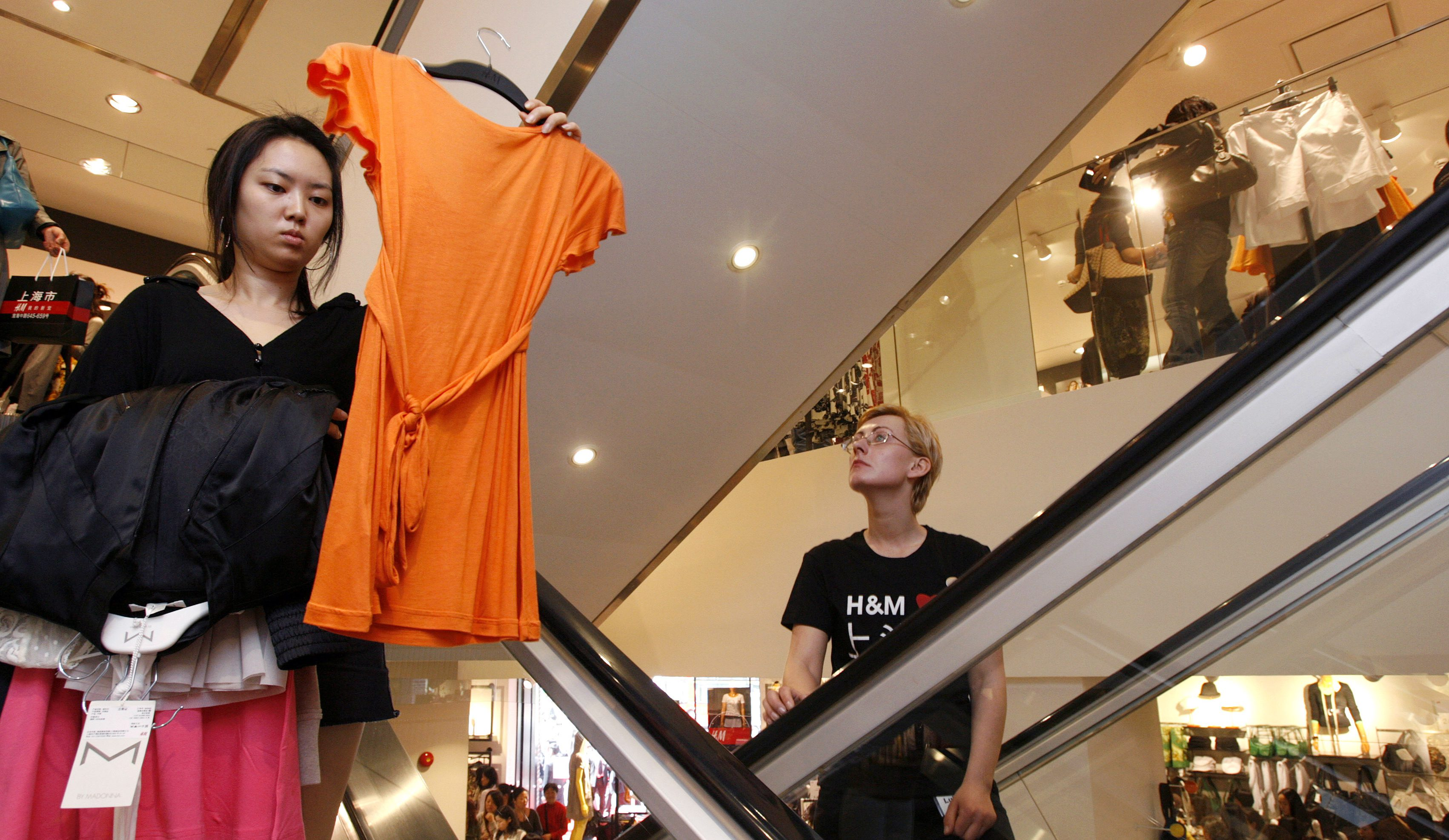 A customer (L) travels down an escalator in the newly opened H&M shop in Shanghai April 12, 2007. Global fashion chain Hennes & Mauritz is planning more stores in Asia and believes that China will eventually be comparable to its European business, its chief executive said on Wednesday. REUTERS/Nir Elias (CHINA) - GM1DVAGLXPAA