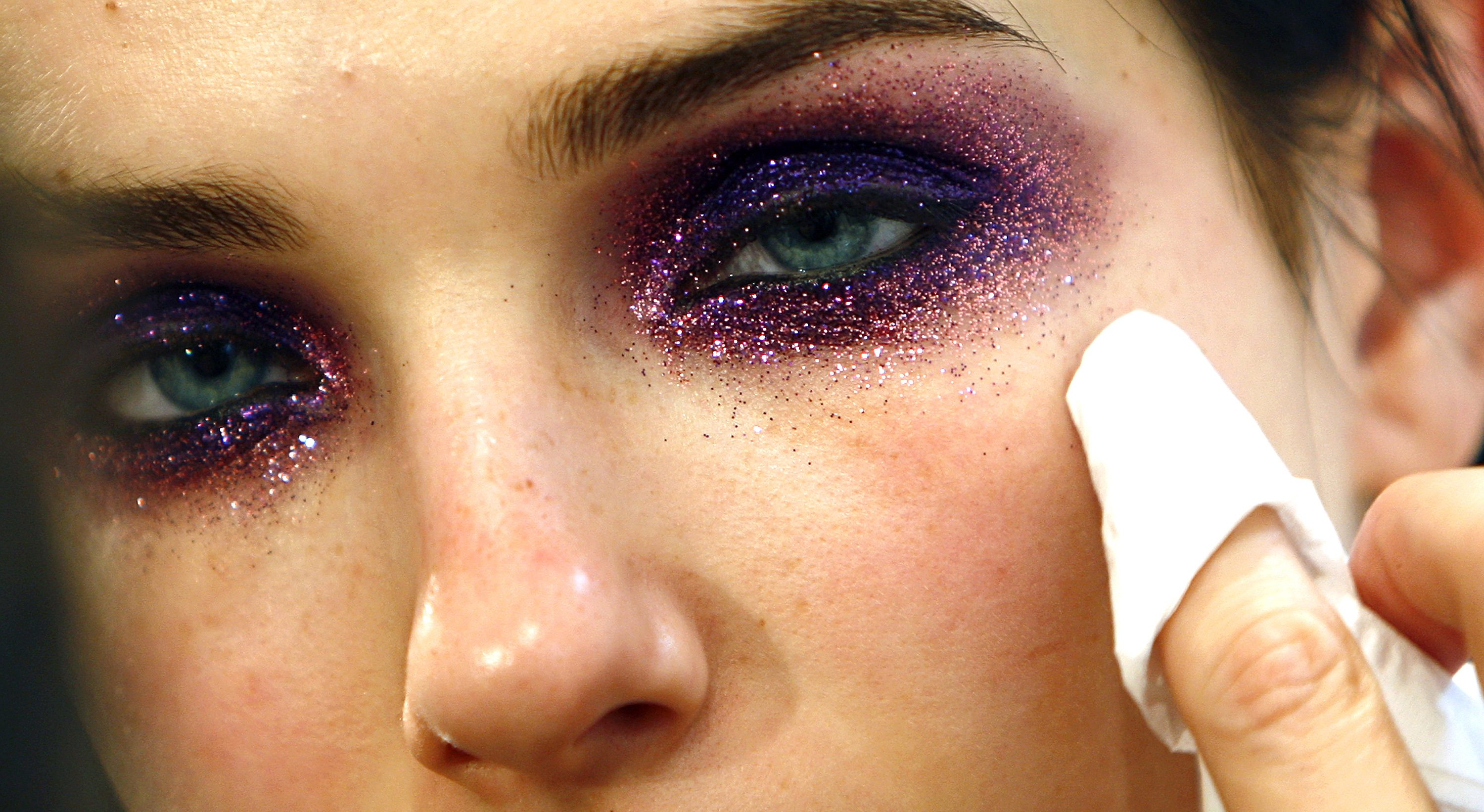 A model has make-up applied on her backstage