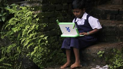 "A school girl uses a laptop provided under the ""One Laptop Per Child' project by a non-governmental organisation (NGO), in a state-run primary school in Khairat"