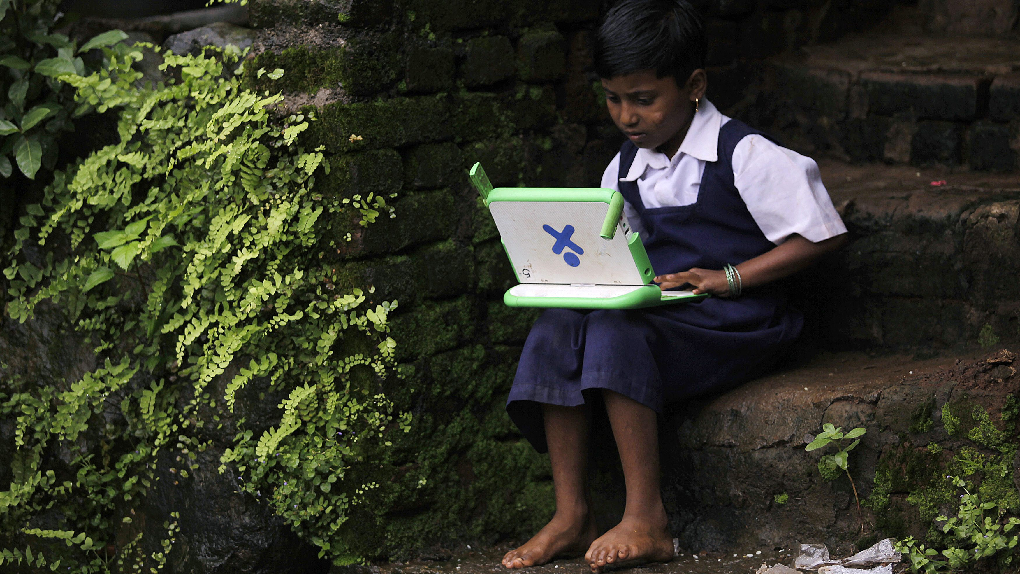 """A school girl uses a laptop provided under the """"One Laptop Per Child' project by a non-governmental organisation (NGO), in a state-run primary school in Khairat"""