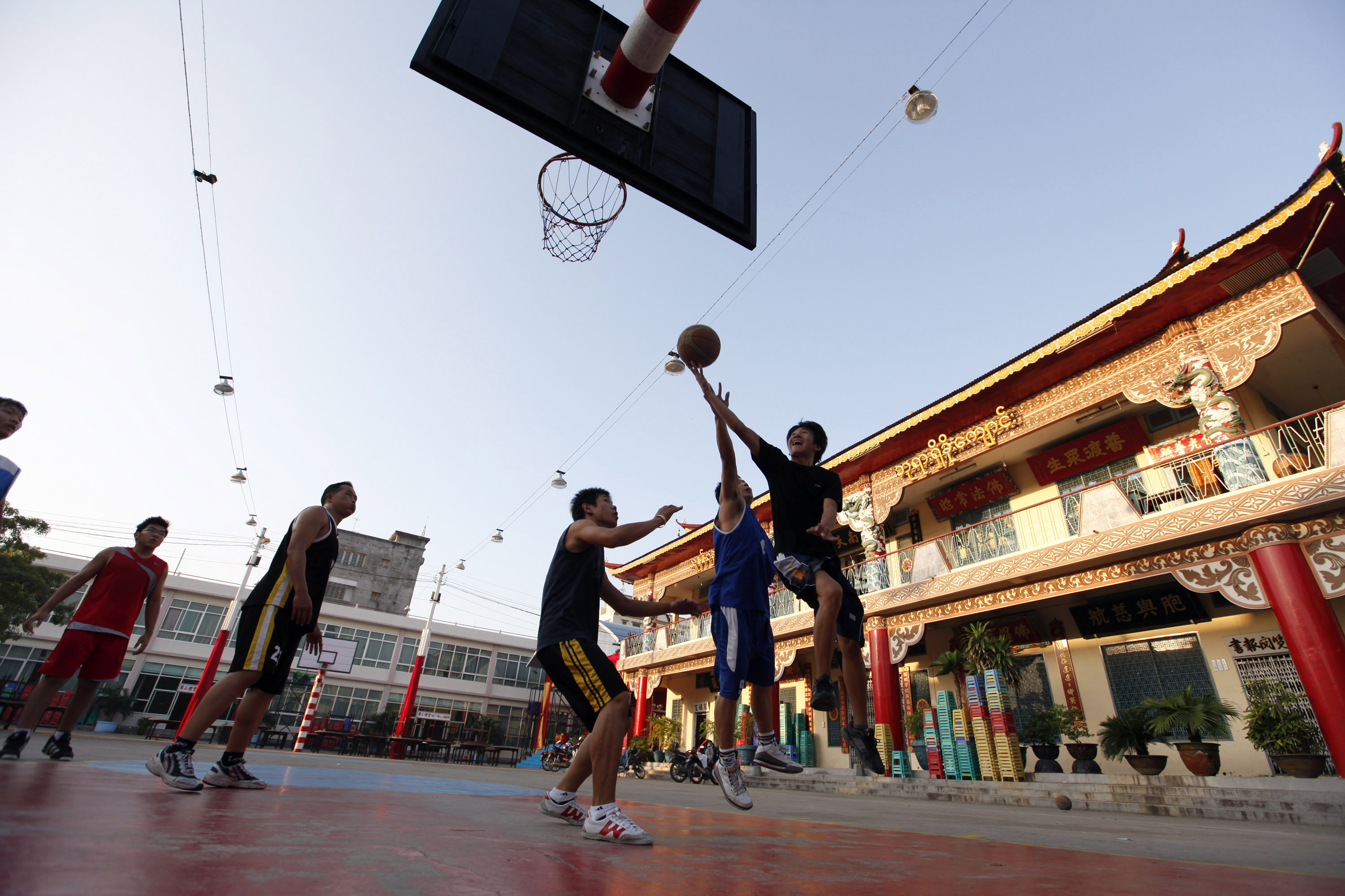Chinese men play basketball at a Chinese communal temple in Mandalay