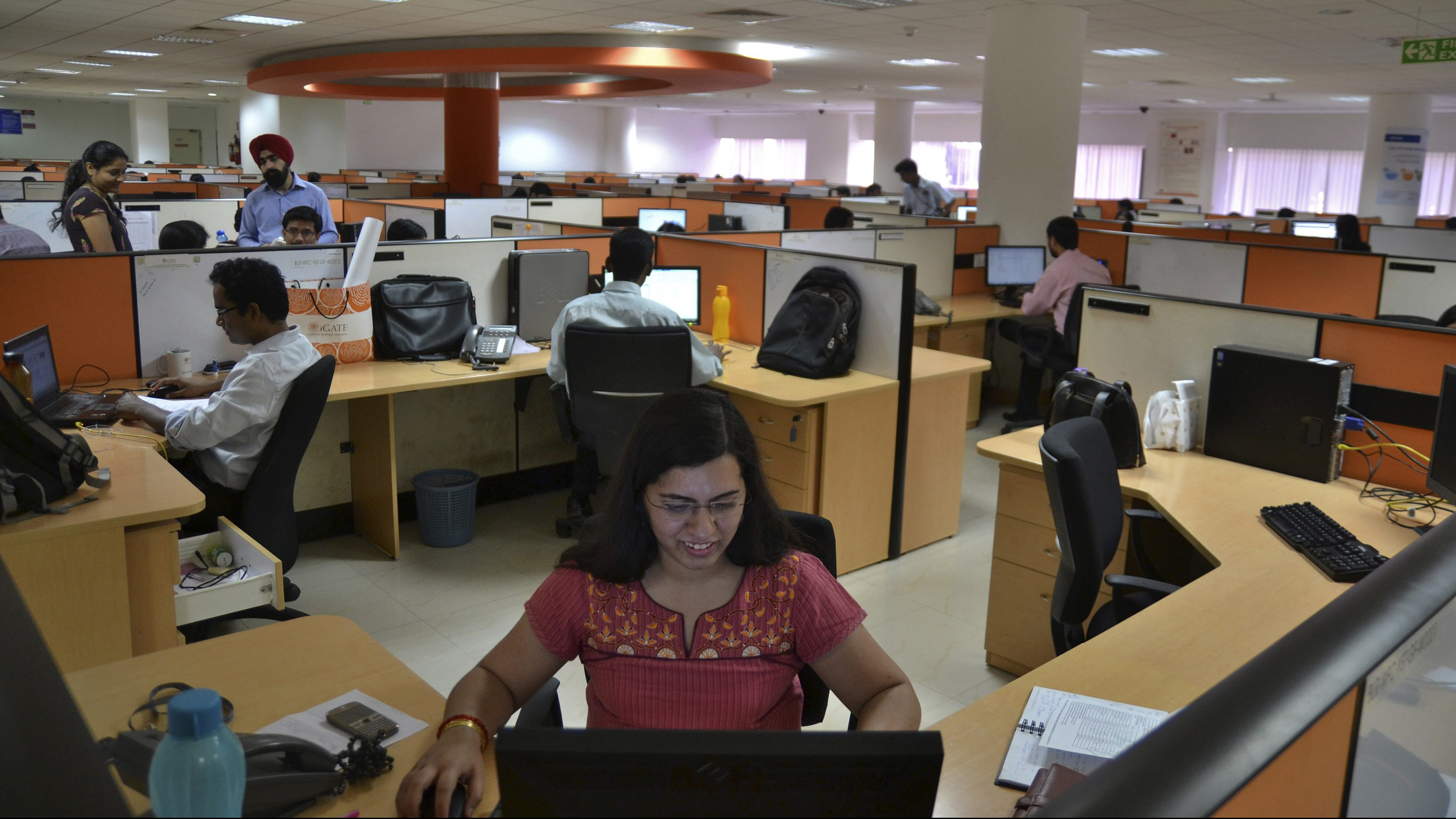 Employees work at the Indian headquarters of iGate in the southern Indian city of Bangalore February 4, 2013. A former Infosys Ltd executive is challenging the IT outsourcing industry's billing model by charging for results instead of basing fees on the time and labour put in by the armies of staff working for India's big firms. Picture taken February 4, 2013. REUTERS/Stringer (INDIA - Tags: BUSINESS SCIENCE TECHNOLOGY) - GM1E92M0E4K01
