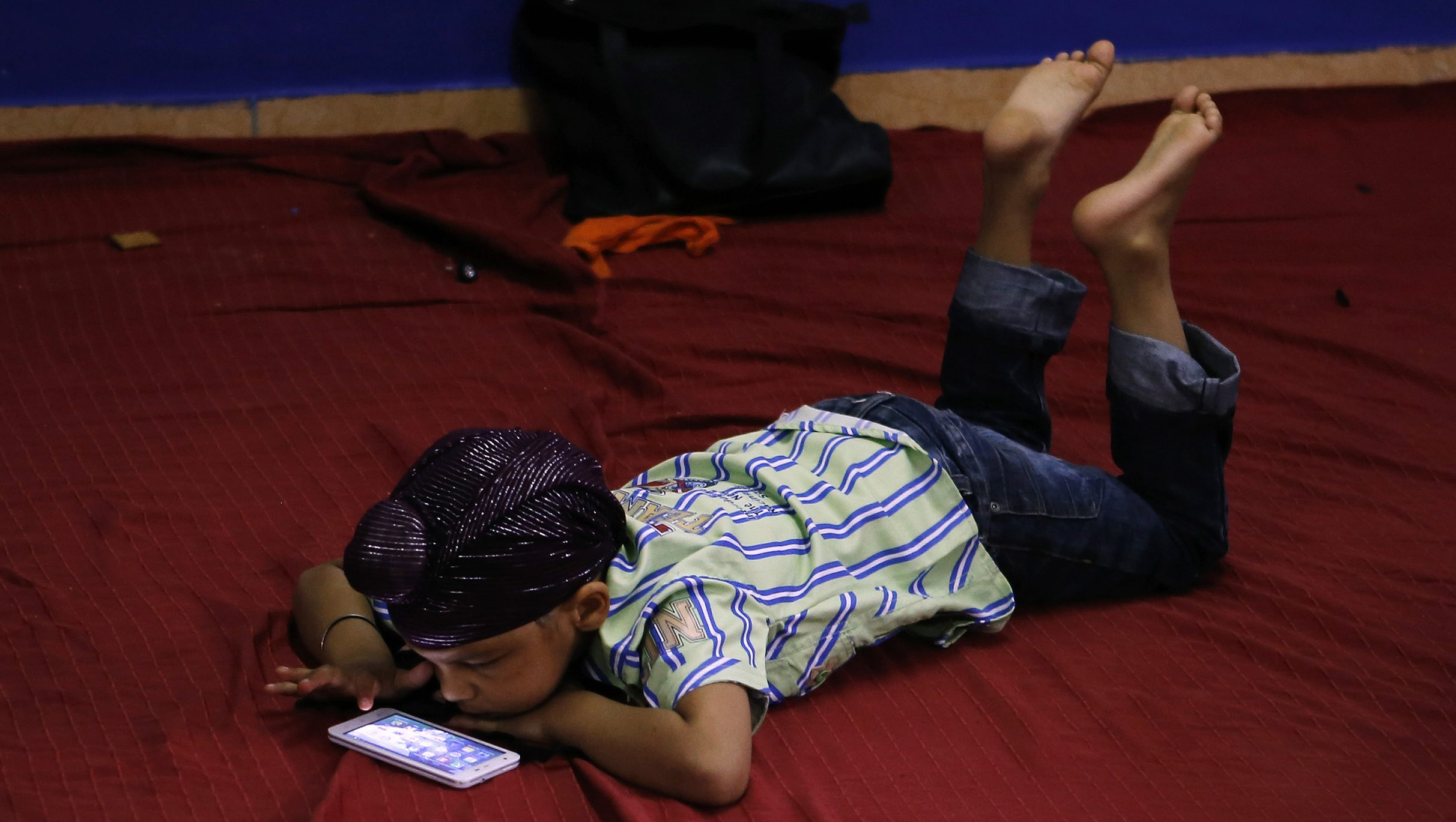 A young Sikh plays with a smartphone inside a Sikh temple during their Baisakhi festival in Palma de Mallorca on the Spanish Balearic island of Mallorca, April 27, 2014. Sikhs celebrate Baisakhi, a harvest festival, as the beginning of the New Year.   REUTERS/Enrique Calvo (SPAIN - Tags: RELIGION SOCIETY) - GM1EA4S01Z201