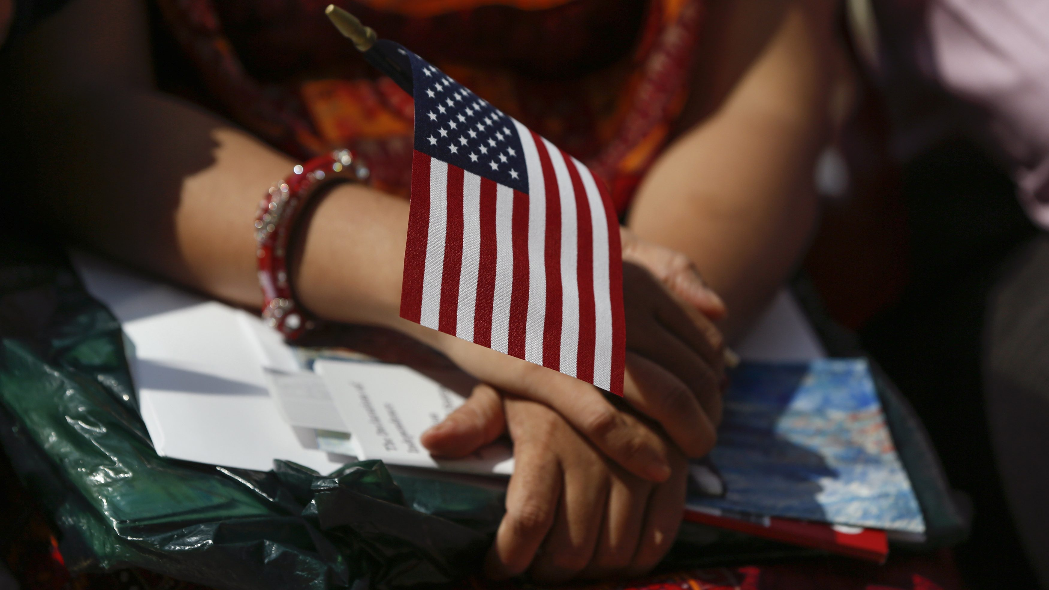 A new American citizen holds a U.S. flag during a naturalization ceremony at The Metropolitan Museum of Art in New York