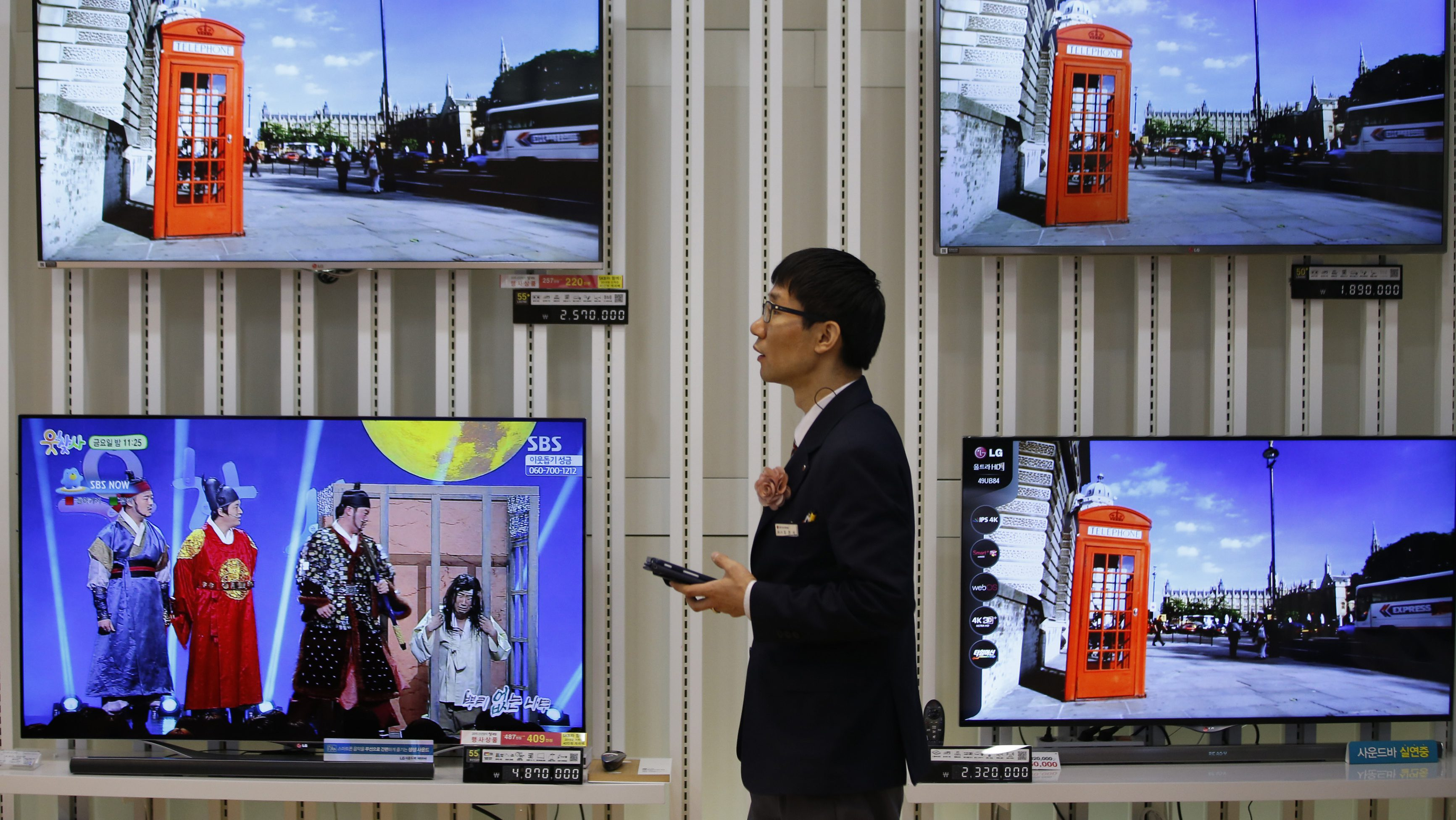 An employee uses his mobile phone in front of LG Electronics' organic light-emitting diode (OLED) TV sets, which are made with LG Display flat screens, at its store in Seoul January 28, 2015. South Korea's LG Display Co Ltd booked its highest quarterly profit in almost four years on Wednesday, buoyed by firm demand for liquid crystal displays (LCD) from television makers and client Apple Inc.   REUTERS/Kim Hong-Ji (SOUTH KOREA - Tags: BUSINESS) - GM1EB1S156O01