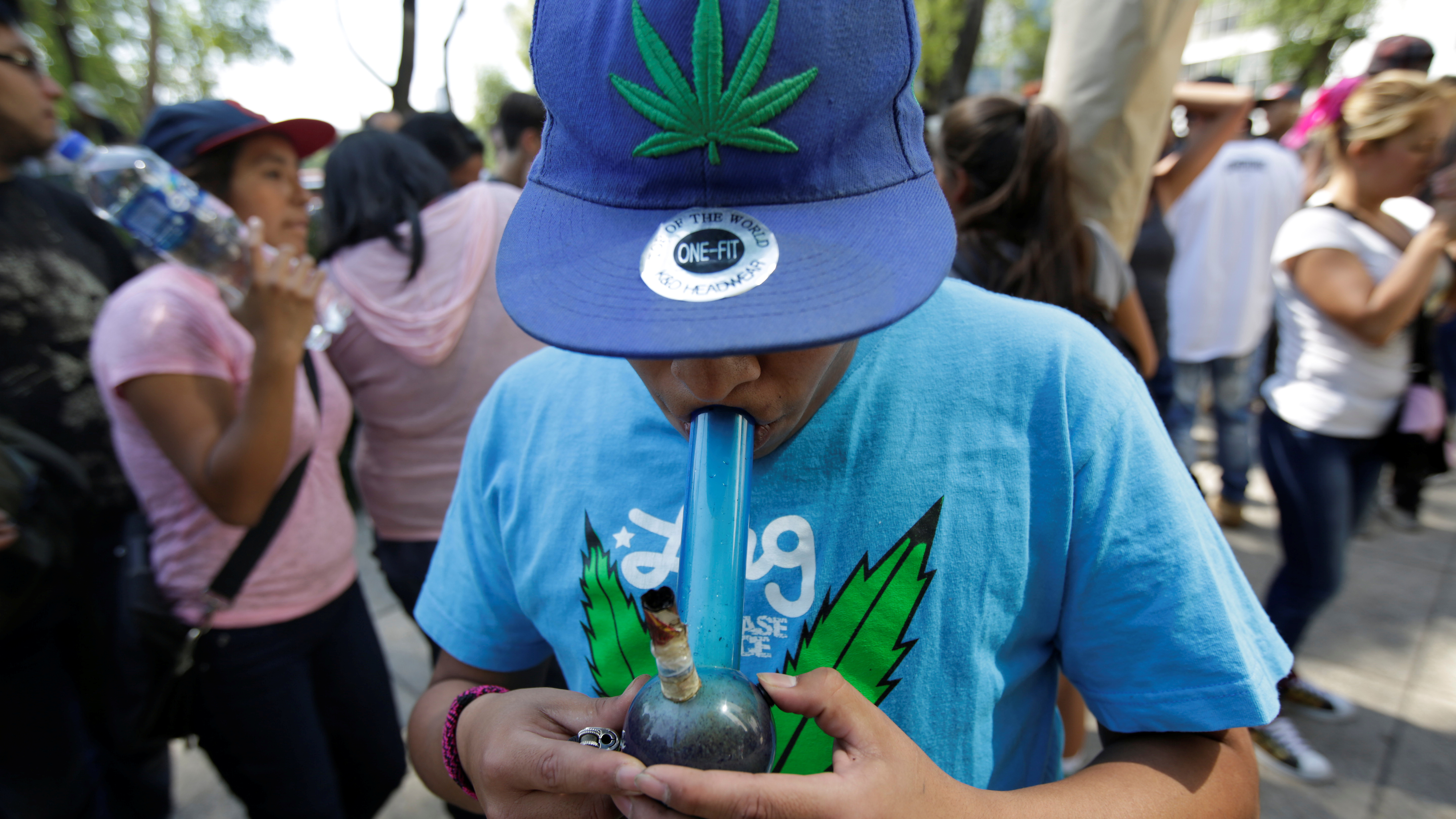A teenager smokes marijuana out of a bong during a 4/20 party to demand legalization and to celebrate marijuana culture outside the Senate building in Mexico City, Mexico, April 20, 2017.  - RC1C3BF47220