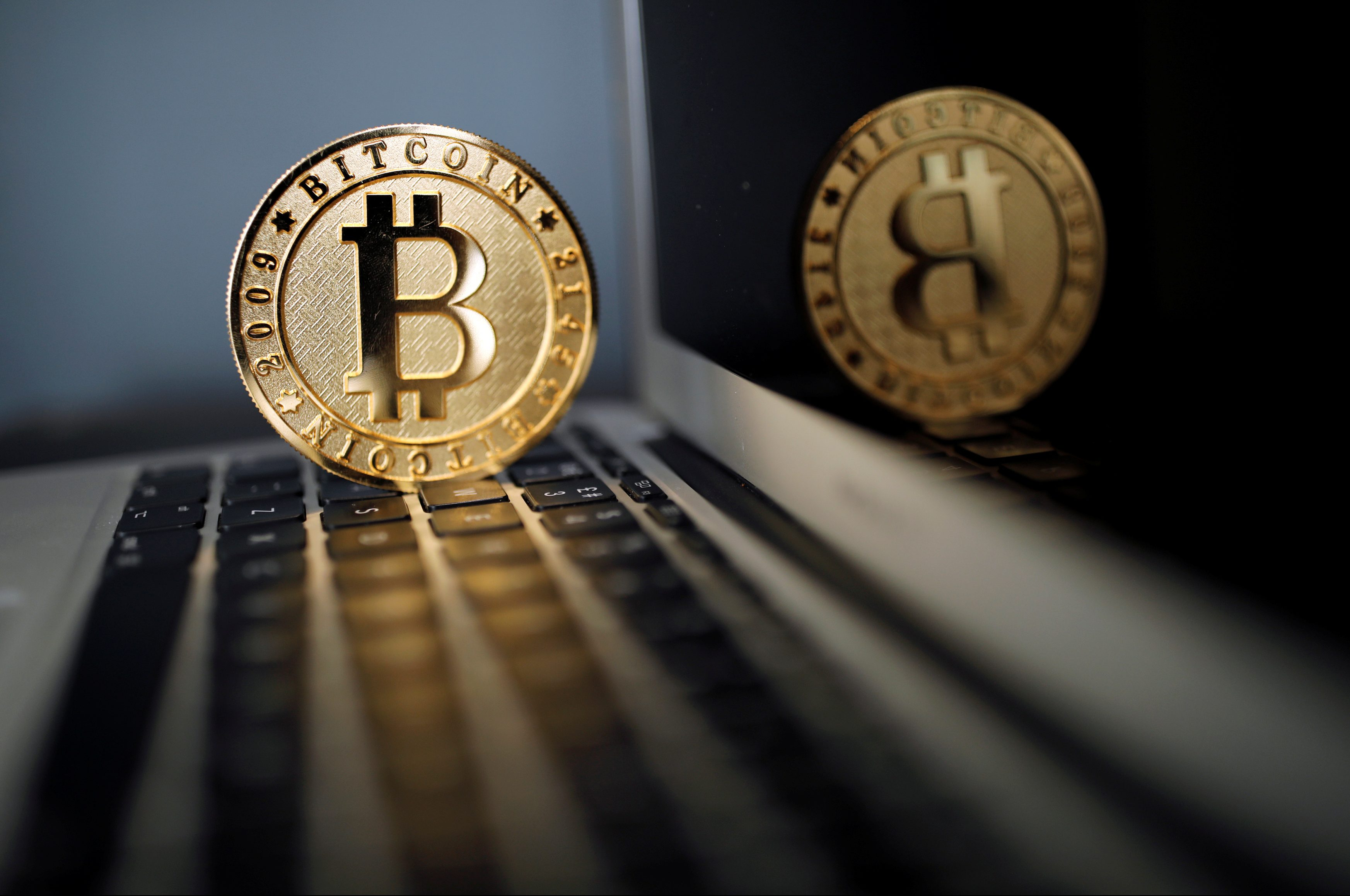 A Bitcoin (virtual currency) coin is seen in an illustration picture taken at La Maison du Bitcoin in Paris, France, June 23, 2017. REUTERS/Benoit Tessier/Illustration - RC14EAB5E9F0