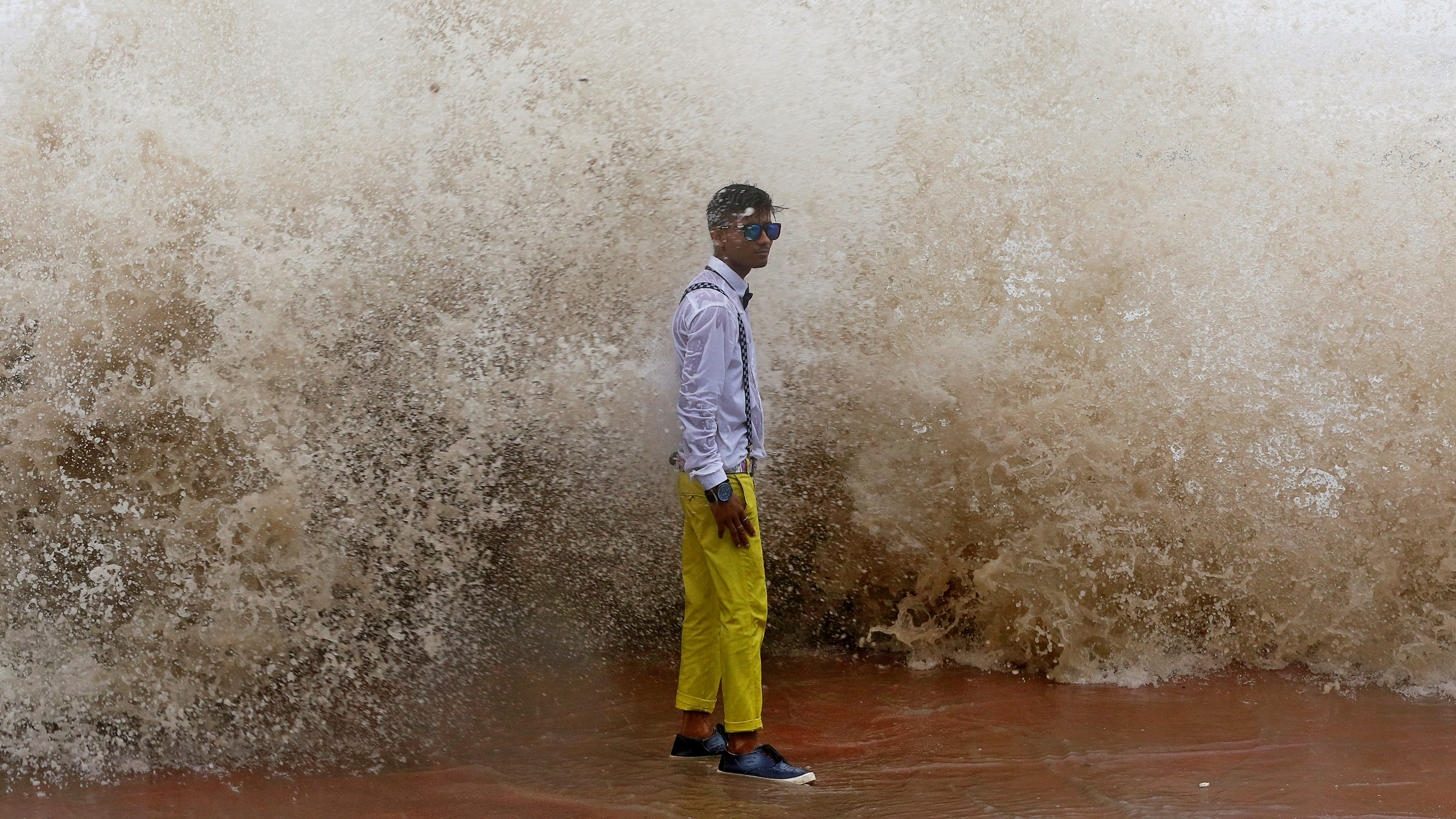 A boy poses for a photograph during a high tide in Mumbai, India June 27, 2017.
