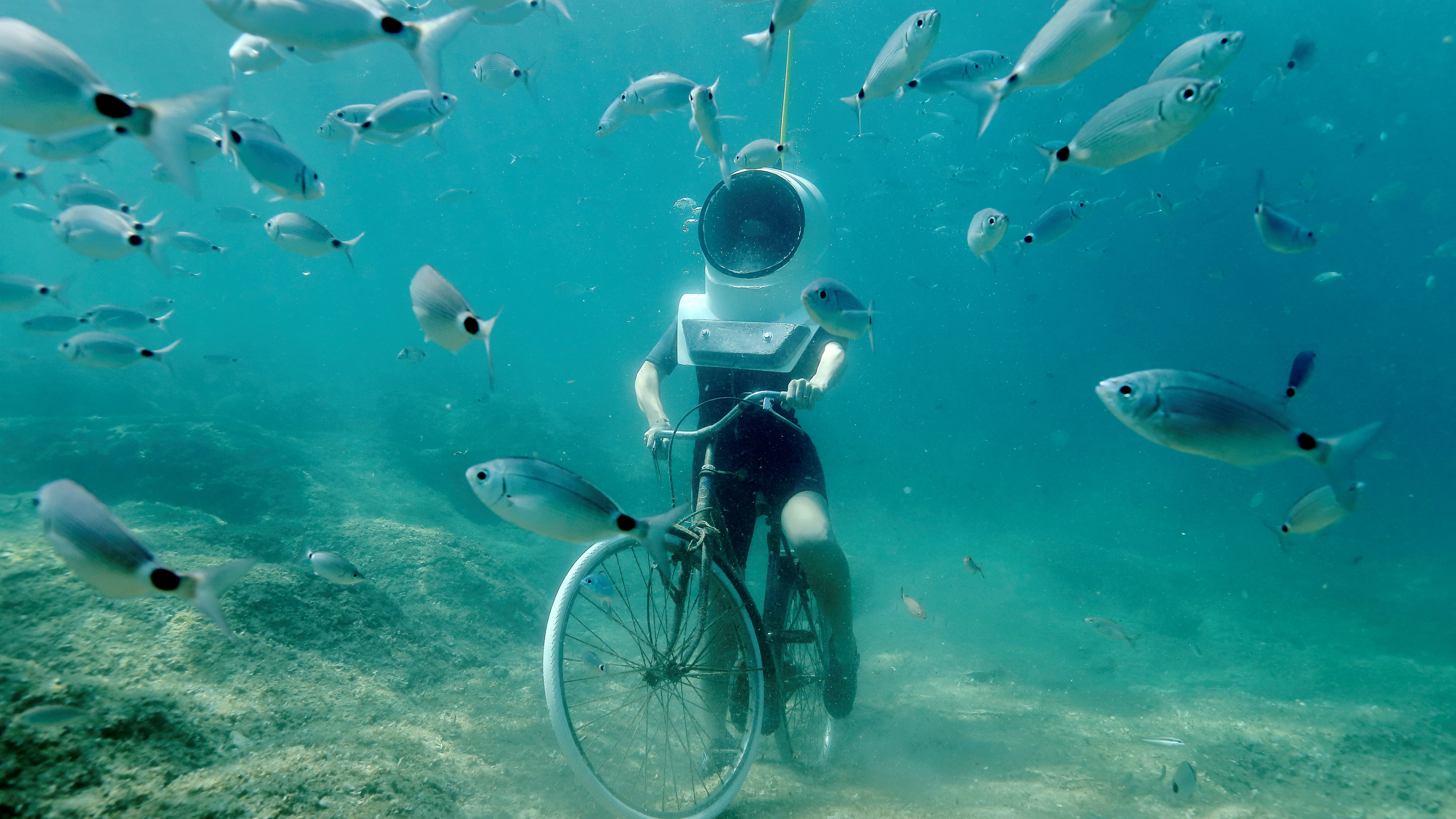 A woman dives and pretends to ride a bike in Underwater Park in Pula, Croatia, August 1, 2017.  - RC14C0F1F570