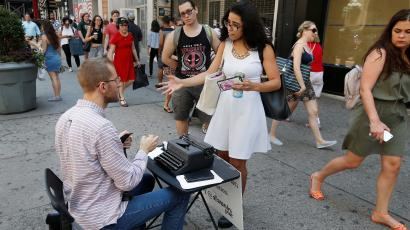 A customer talks to street poet Allan Andre, who writes impromptu poems on an old typewriter, in New York City