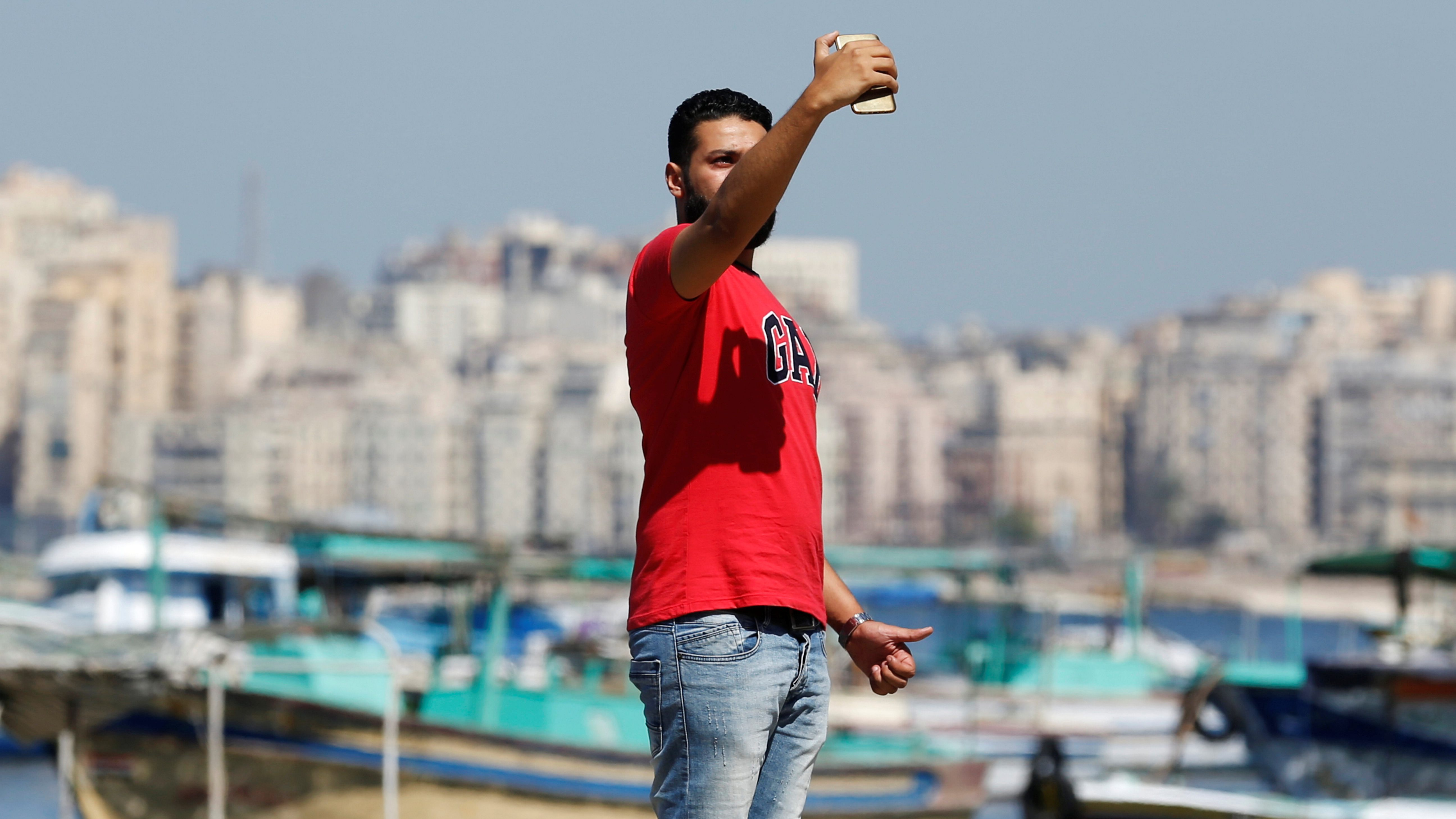 A man takes a selfie picture with his mobile phone along the coast in the Mediterranean city of Alexandria, Egypt