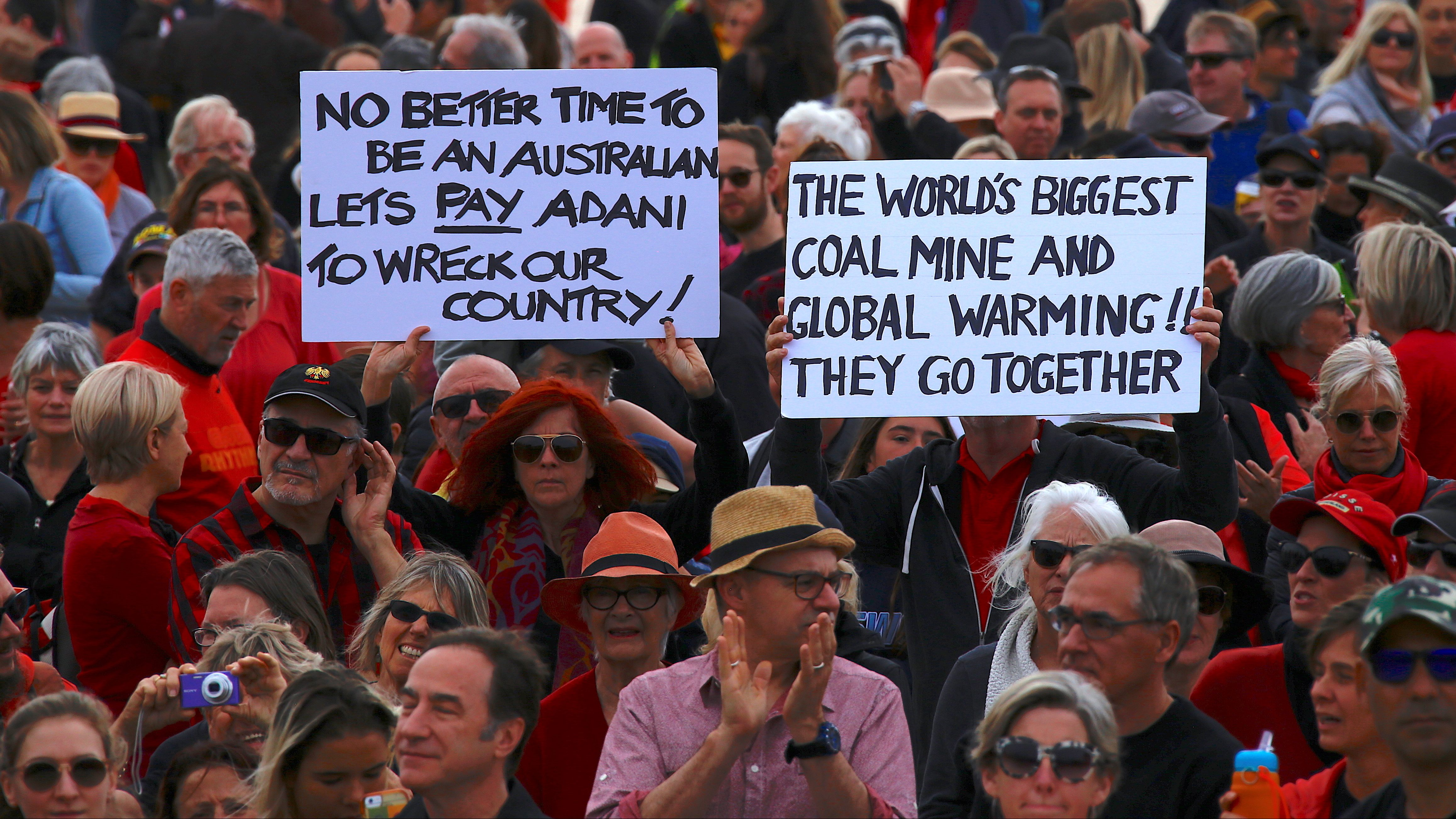 Protesters hold signs as they participate in a national Day of Action against the Indian mining company Adani's planned coal mine project in north-east Australia, at Sydney's Bondi Beach in Australia, October 7, 2017.       - RC18A67A28F0