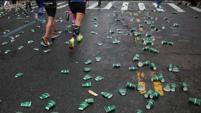 Discarded cups are seen along the route as runners make their way through the borough of Brooklyn during the New York City Marathon in New York.