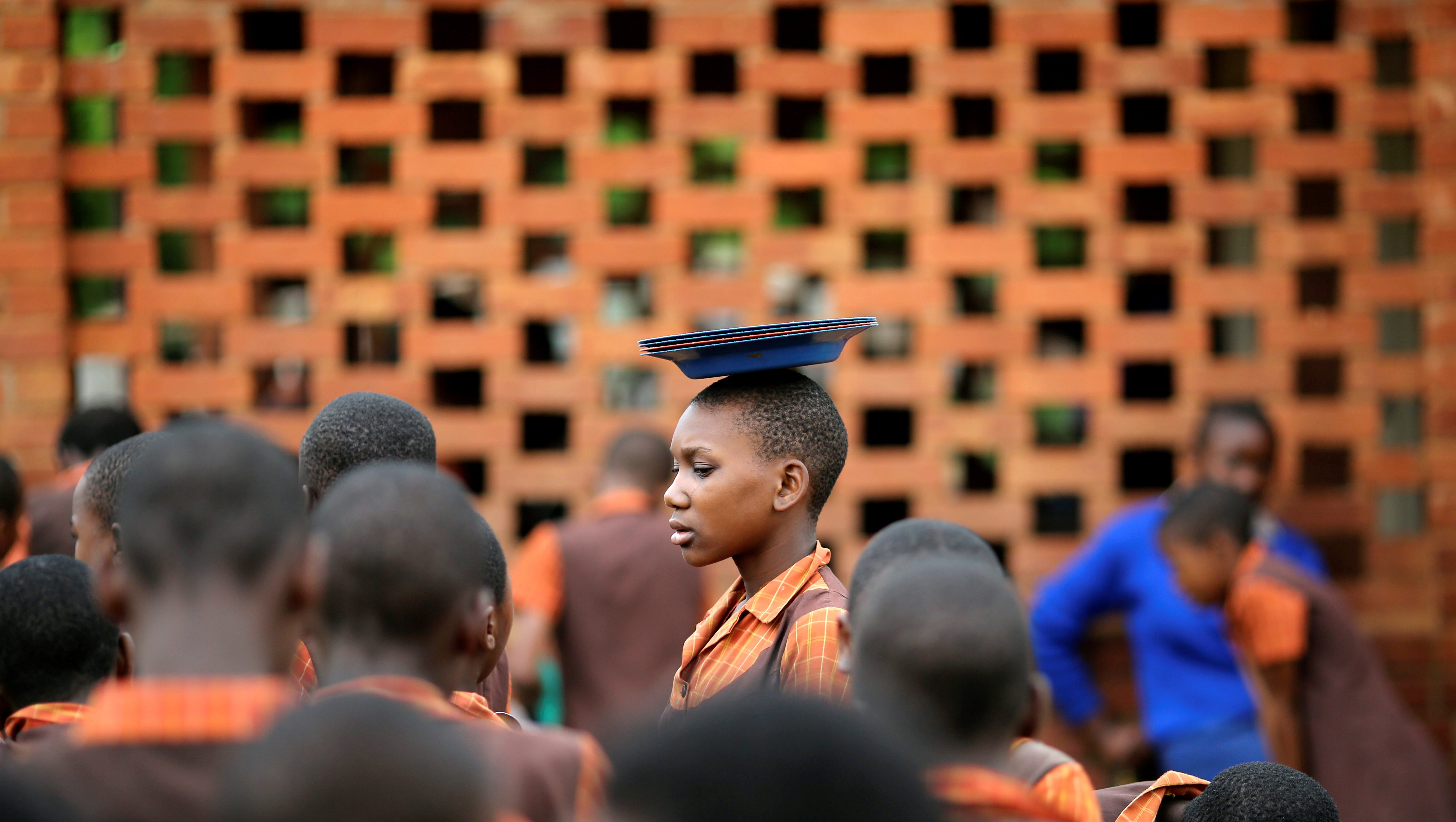 A school child carries plates on her head at Chishawasha Mission Primary School, 27 km east of the capital Harare, Zimbabwe, November 26, 2017.