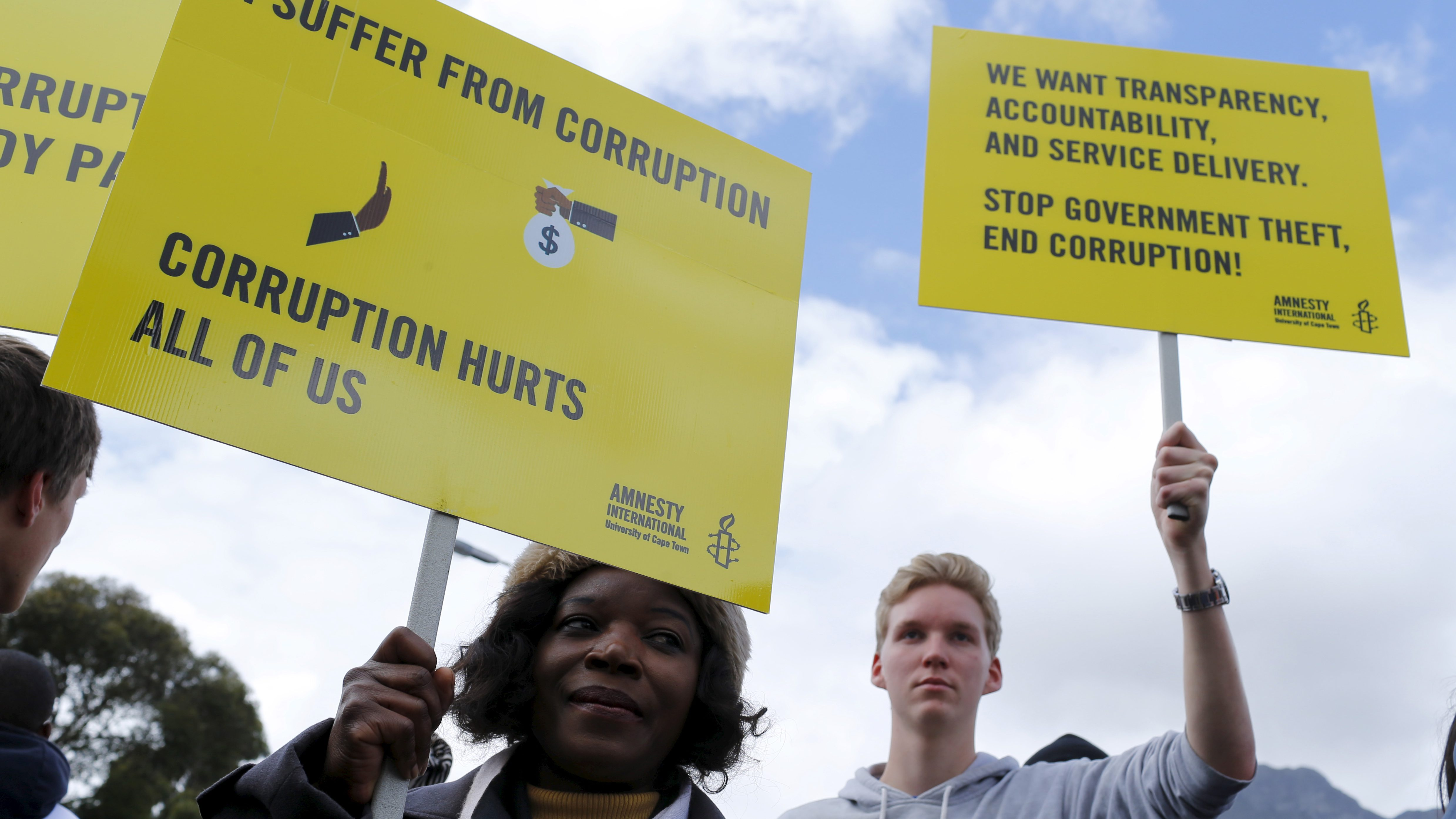 Demonstrators carry placards as they march to protest against corruption in Cape Town