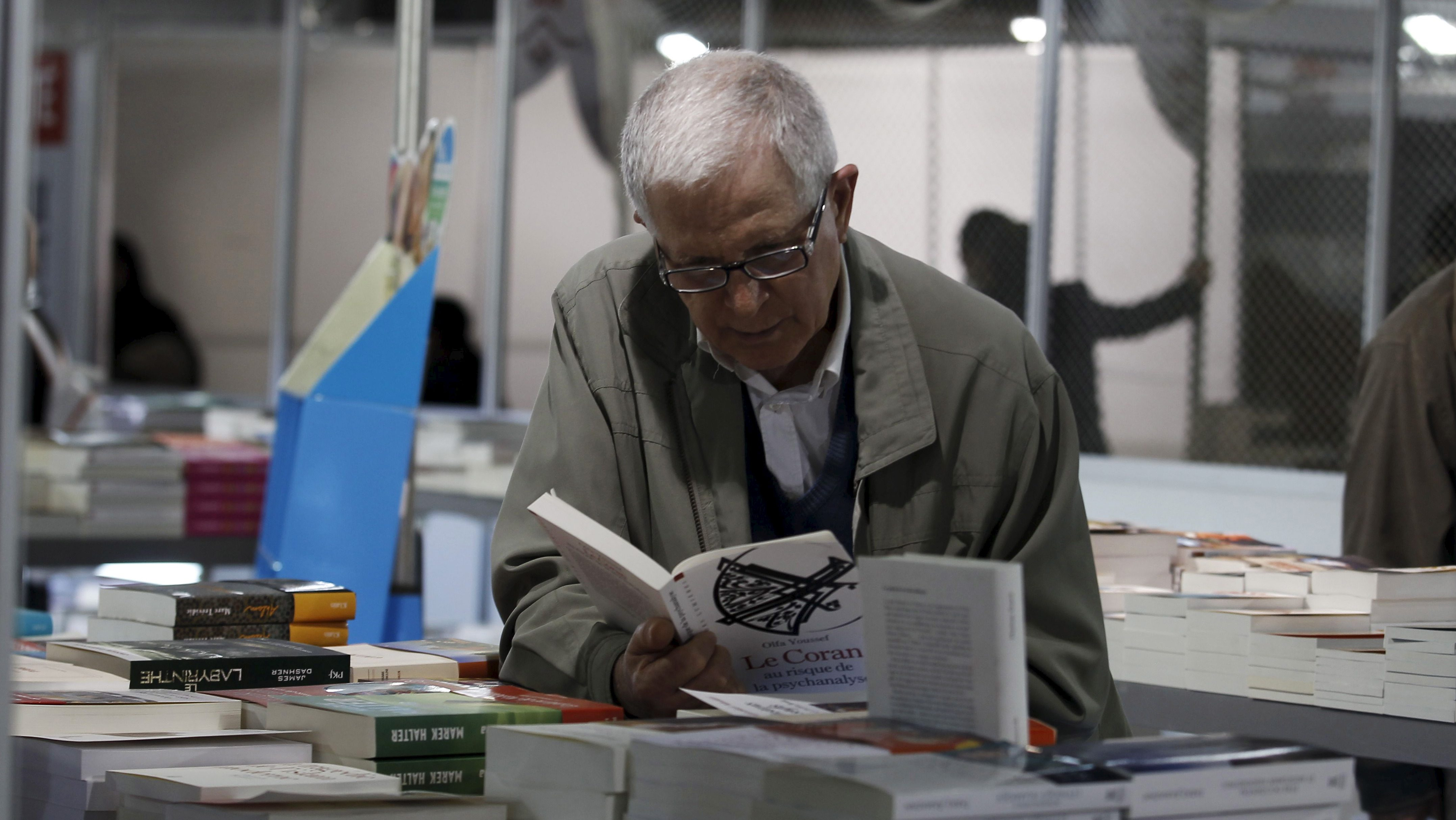 A man reads a book at the 32nd International Book Fair in Tunis, Tunisia, March 25, 2016.