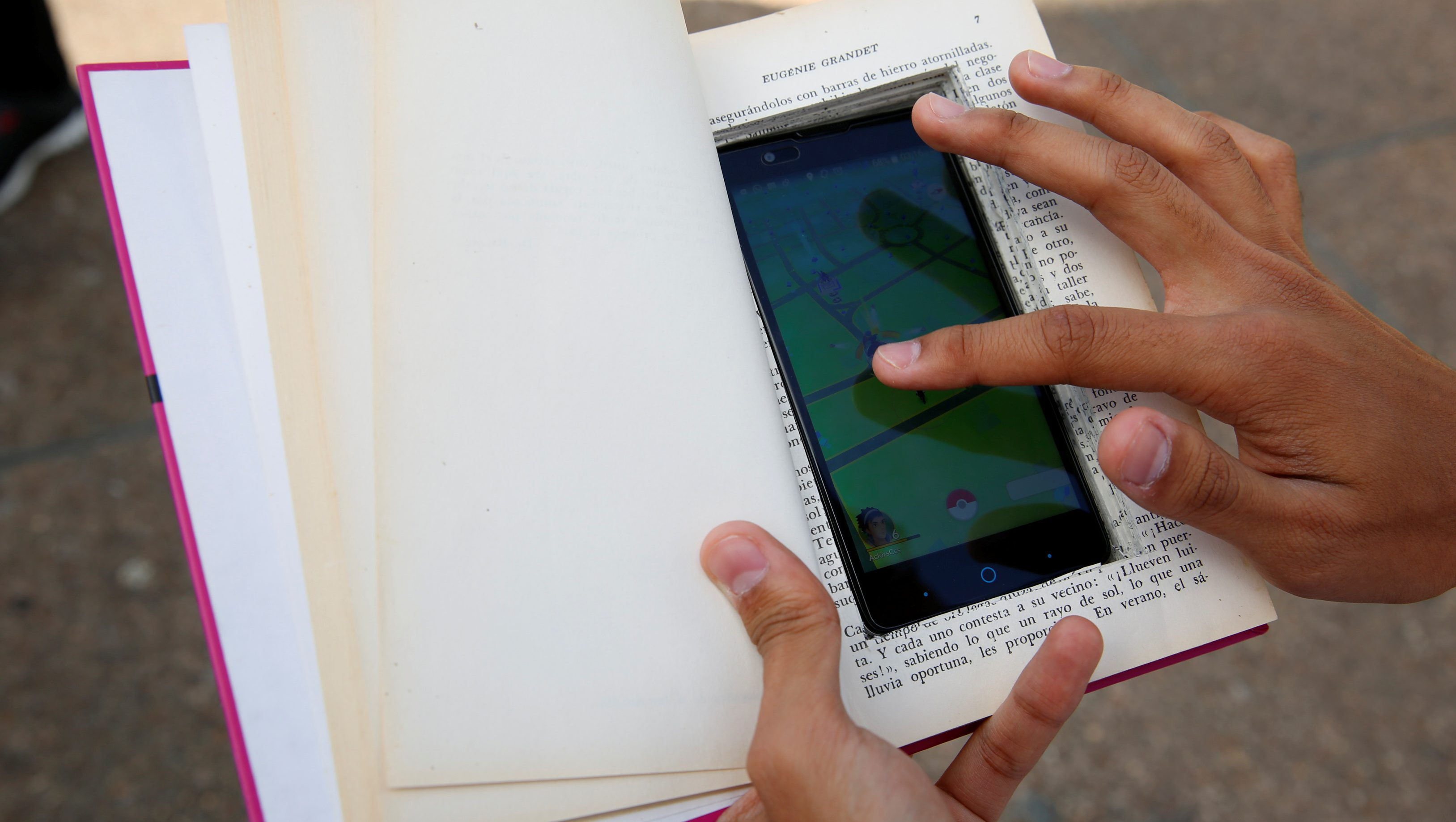 """Carlos Reina plays the augmented reality mobile game """"Pokemon Go"""" with his cell phone camouflaged in a book due to concerns about theft in Caracas, Venezuela August 9, 2016. REUTERS/Carlos Garcia Rawlins - S1BETUQWWMAA"""