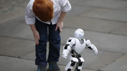 The Alpha 1S Robot is observed by Tristan Robertson-Jeyes, aged five.