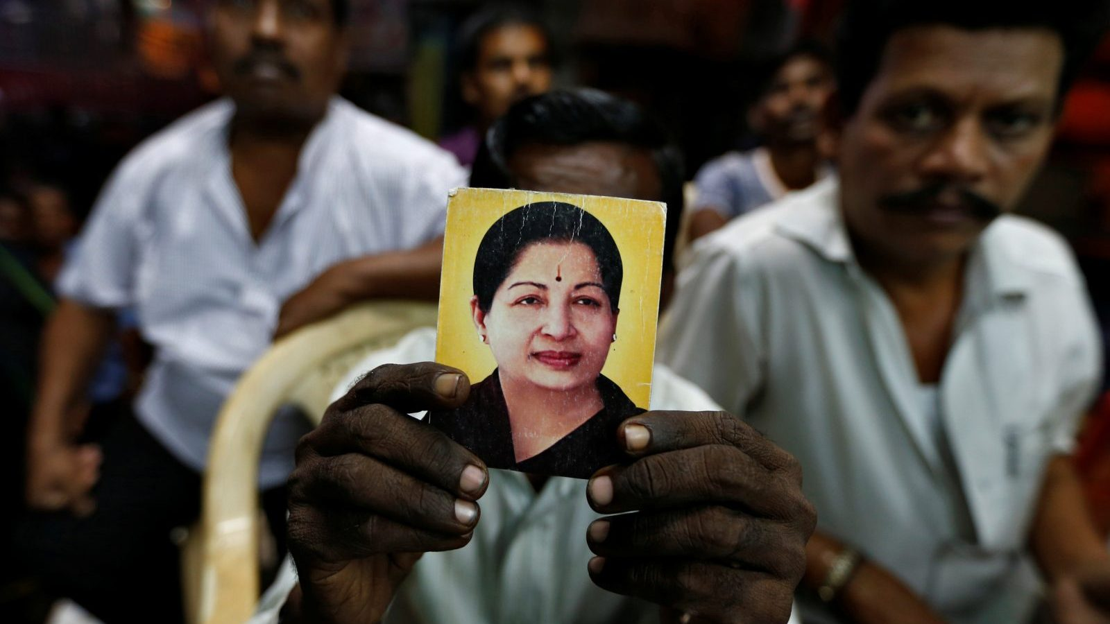 A supporter of Tamil Nadu Chief Minister Jayalalithaa Jayaraman holds her photo at the AIADMK party office in Mumbai, India, December 5, 2016. REUTERS/Danish Siddiqui - RC1571412880