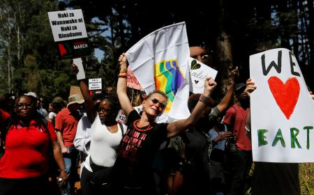 Demonstrators chant slogans and hold banners in protest against U.S. President Donald Trump's during the Women's March inside Karura forest in Kenya's capital Nairobi.