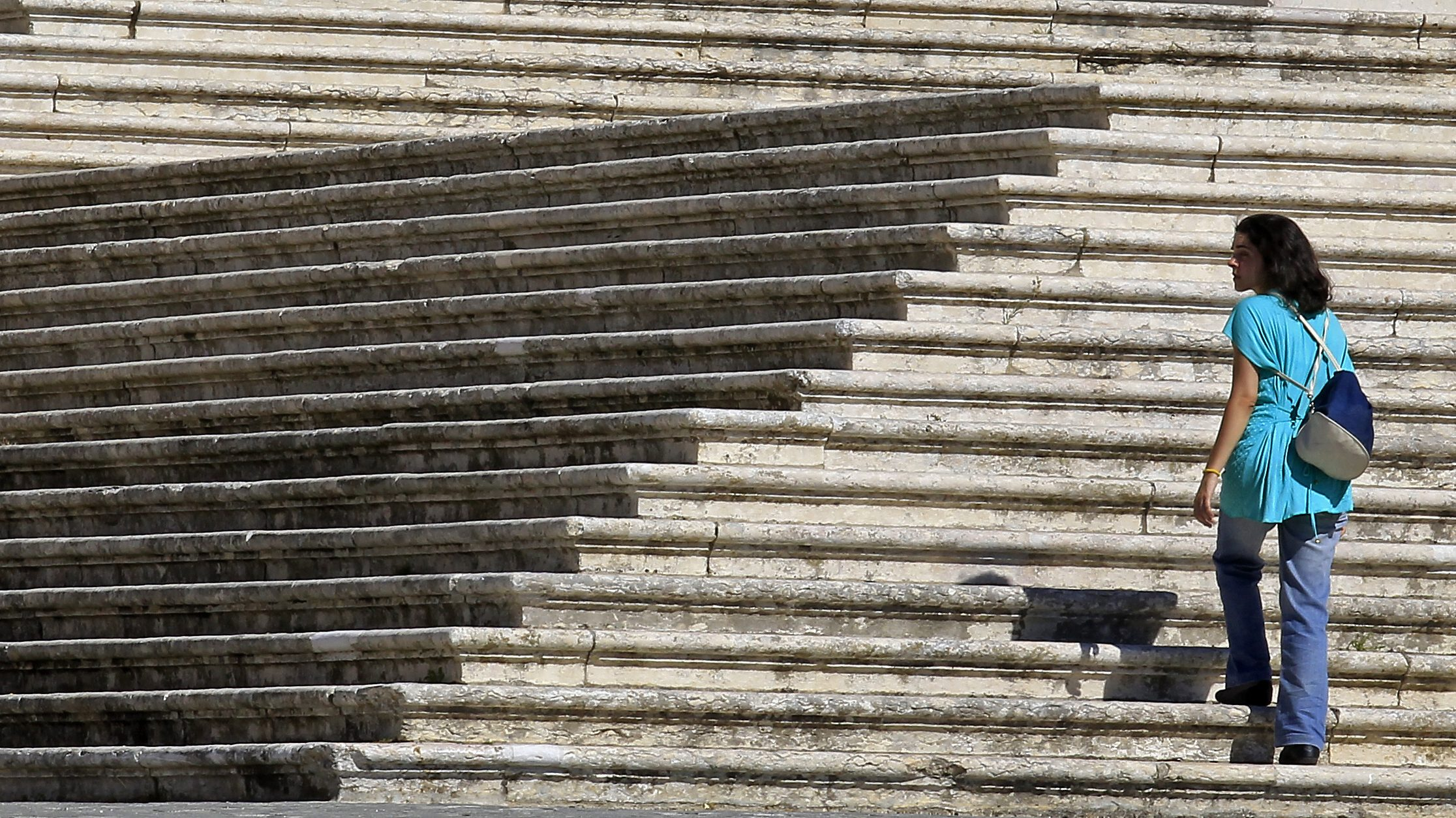 A woman walks up the steps of the Mafra National Palace, north of Lisbon