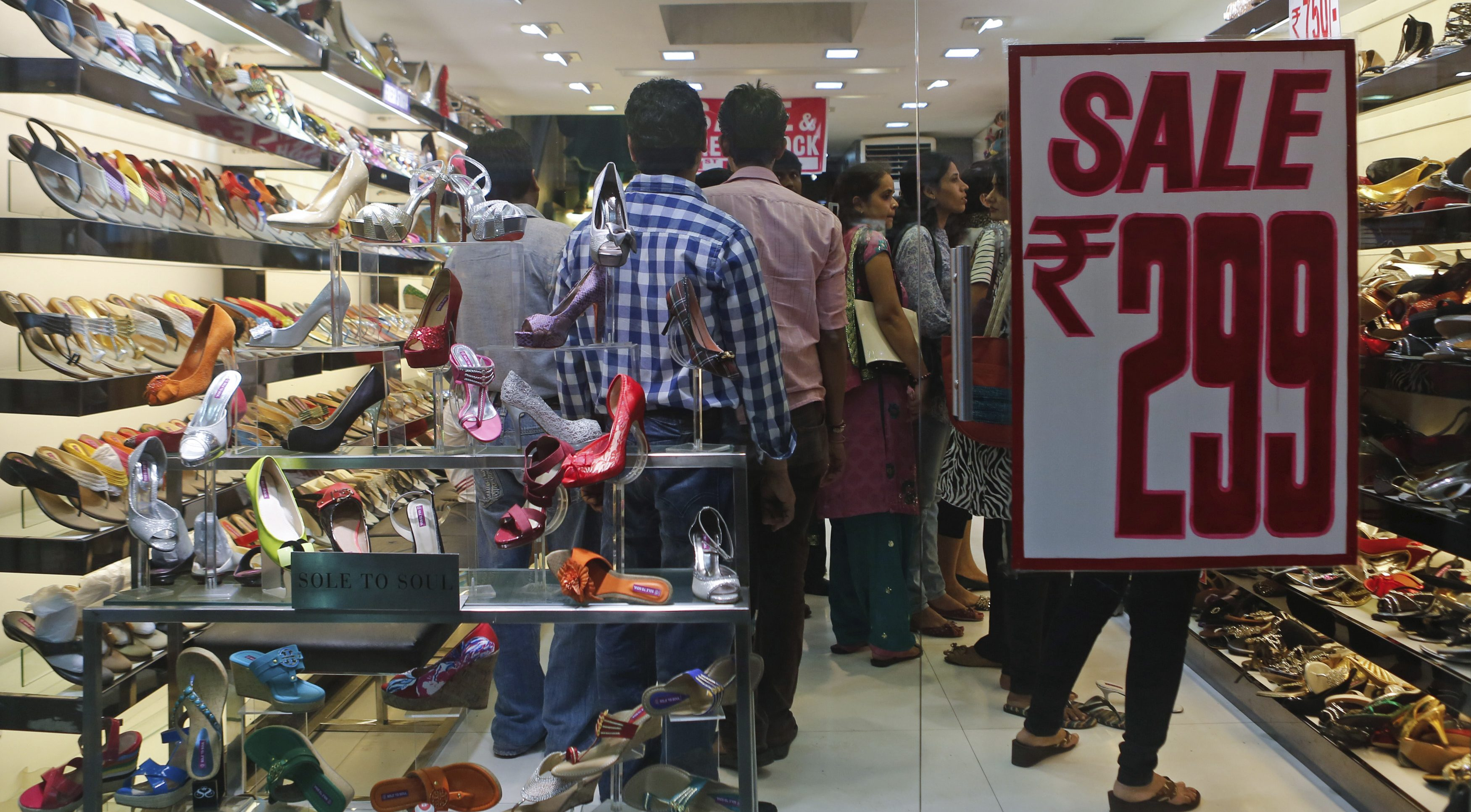 People shop inside a shoe store on a street in Mumbai September 11, 2013. In a capitulation that speaks to the depth of the slump in India's economy, usually tight-fisted retail landlords have become uncharacteristically flexible on rents. Retailers in India say they can now negotiate revenue sharing deals or discounts on rent of up to 20 percent and many are jumping at the chance, not necessarily because they see a bottom to the economic downturn but because the supply of new retail space is expected to tighten sharply from 2015. Picture taken September 11, 2013.          To match INDIA-RETAIL/REALESTATE