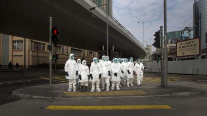 Health officers in full protective gear wait to cross a road near a wholesale poultry market in Hong Kong January 28, 2014.