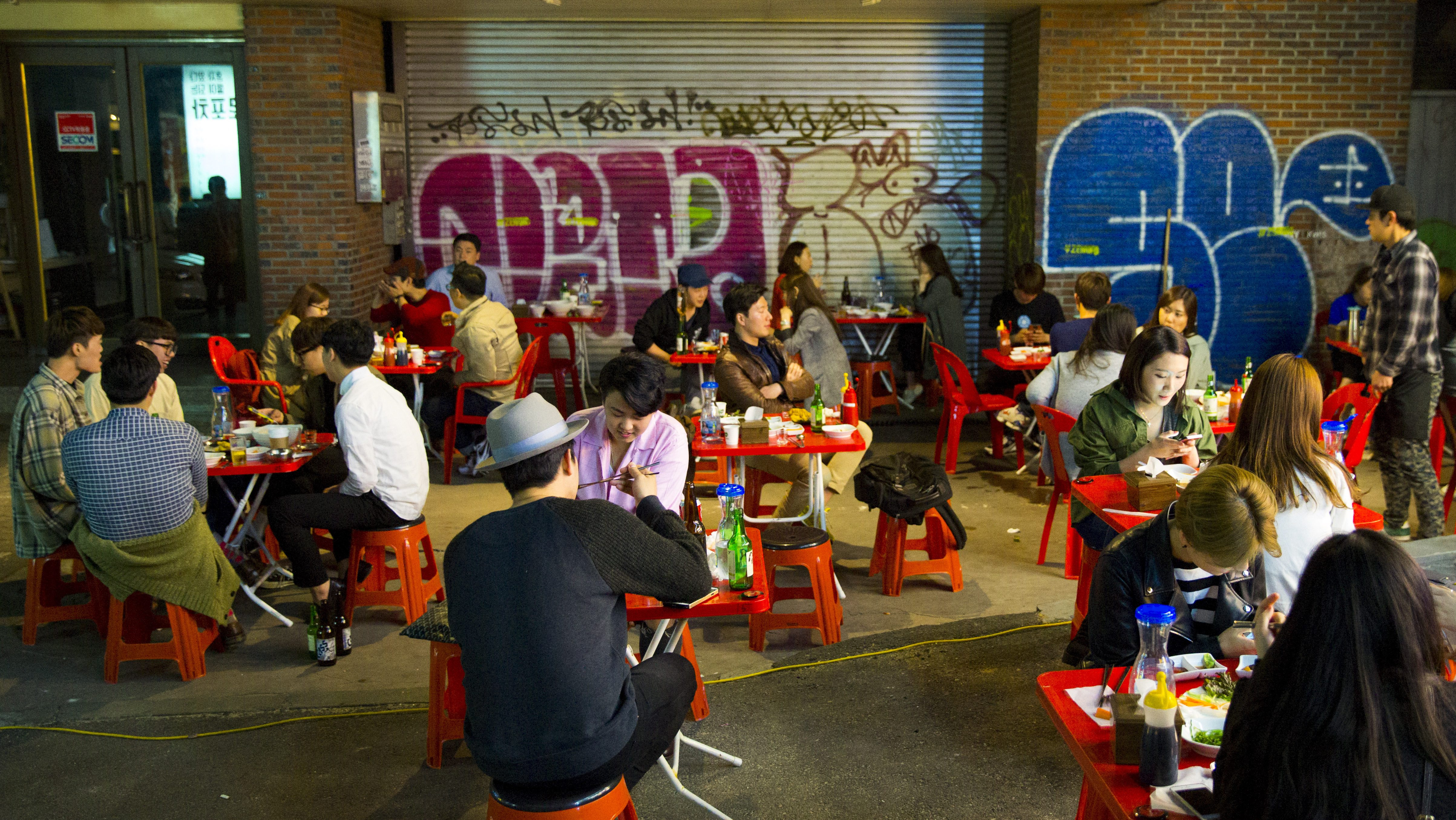 People sit in a streat restaurant in the trendy nightlife district of Hongdae in Seoul, May 9, 2015.