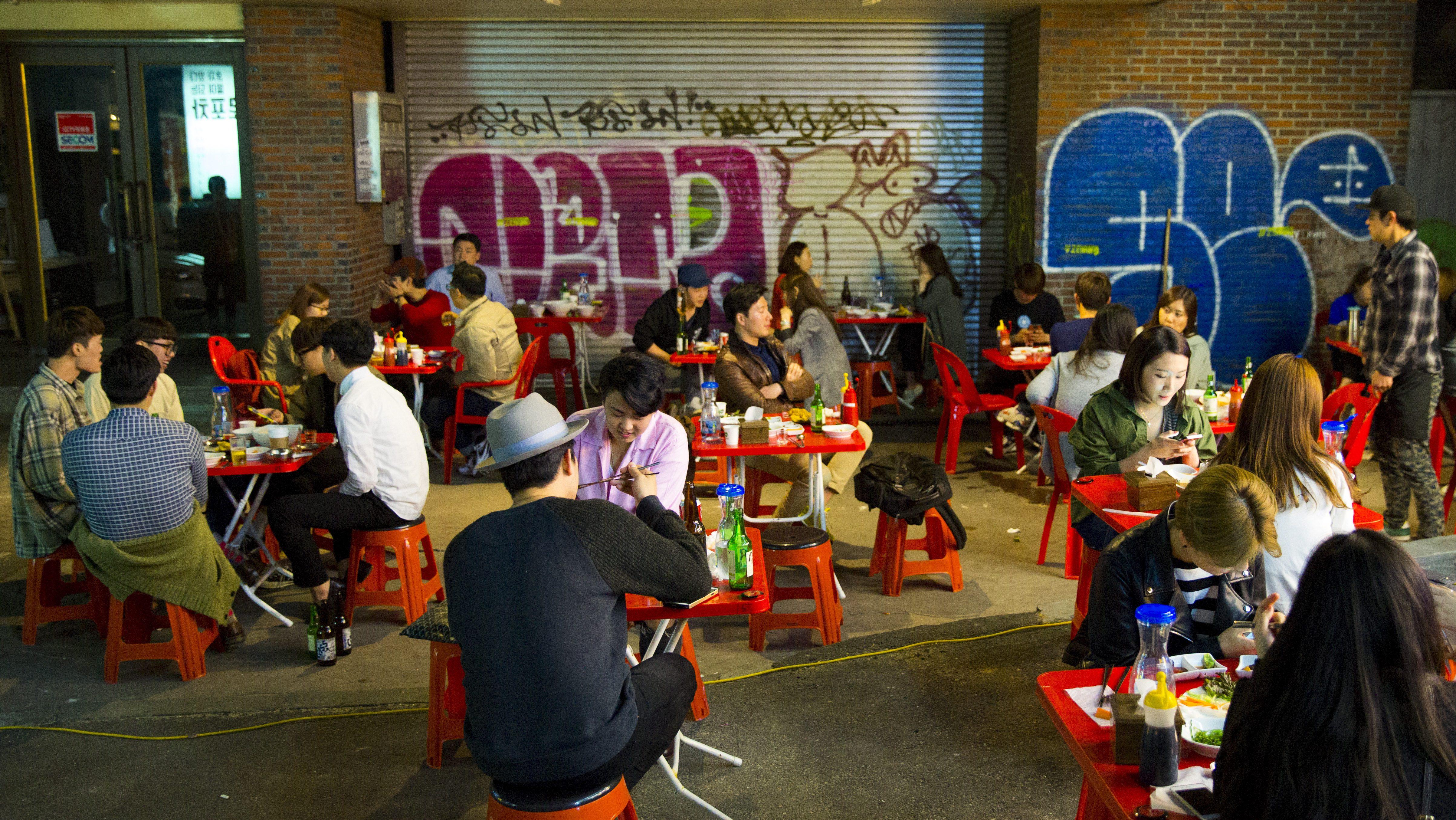 People sit in a streat restaurant in the trendy nightlife district of Hongdae in Seoul, May 9, 2015.