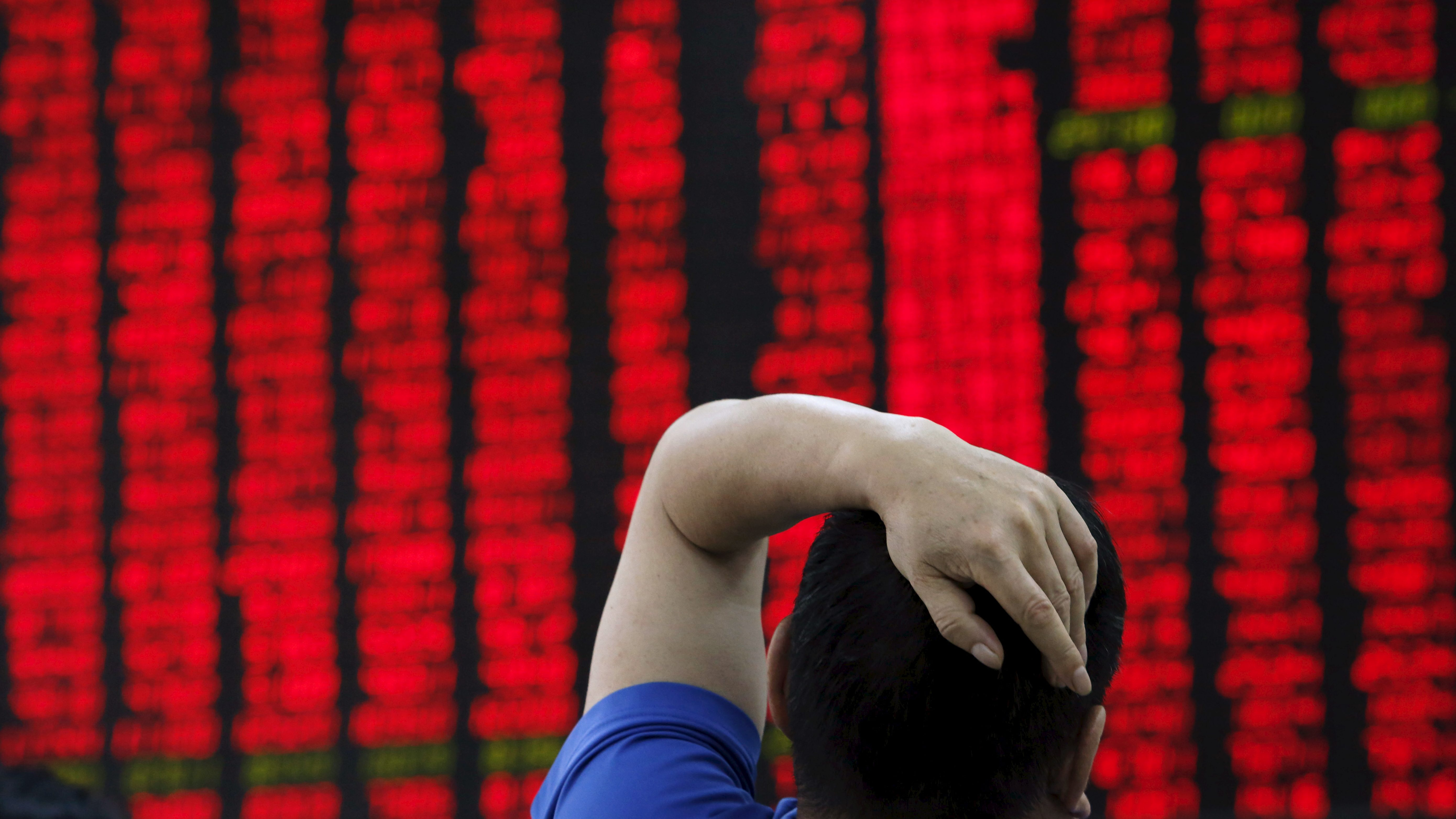 A man watches a board showing stock prices at a brokerage office in Beijing, China, July 1, 2015.