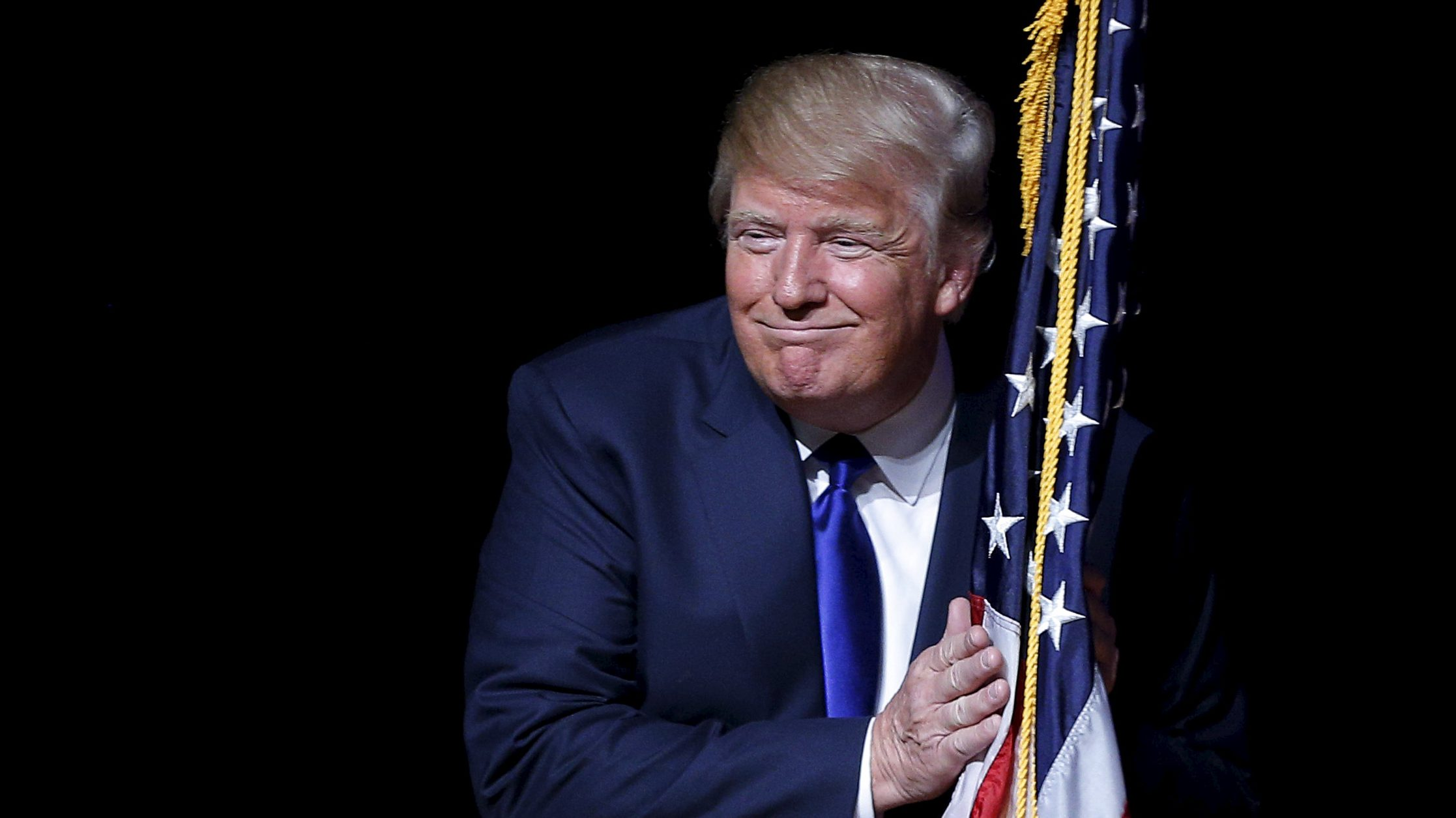 Donald Trump grinning with a flag