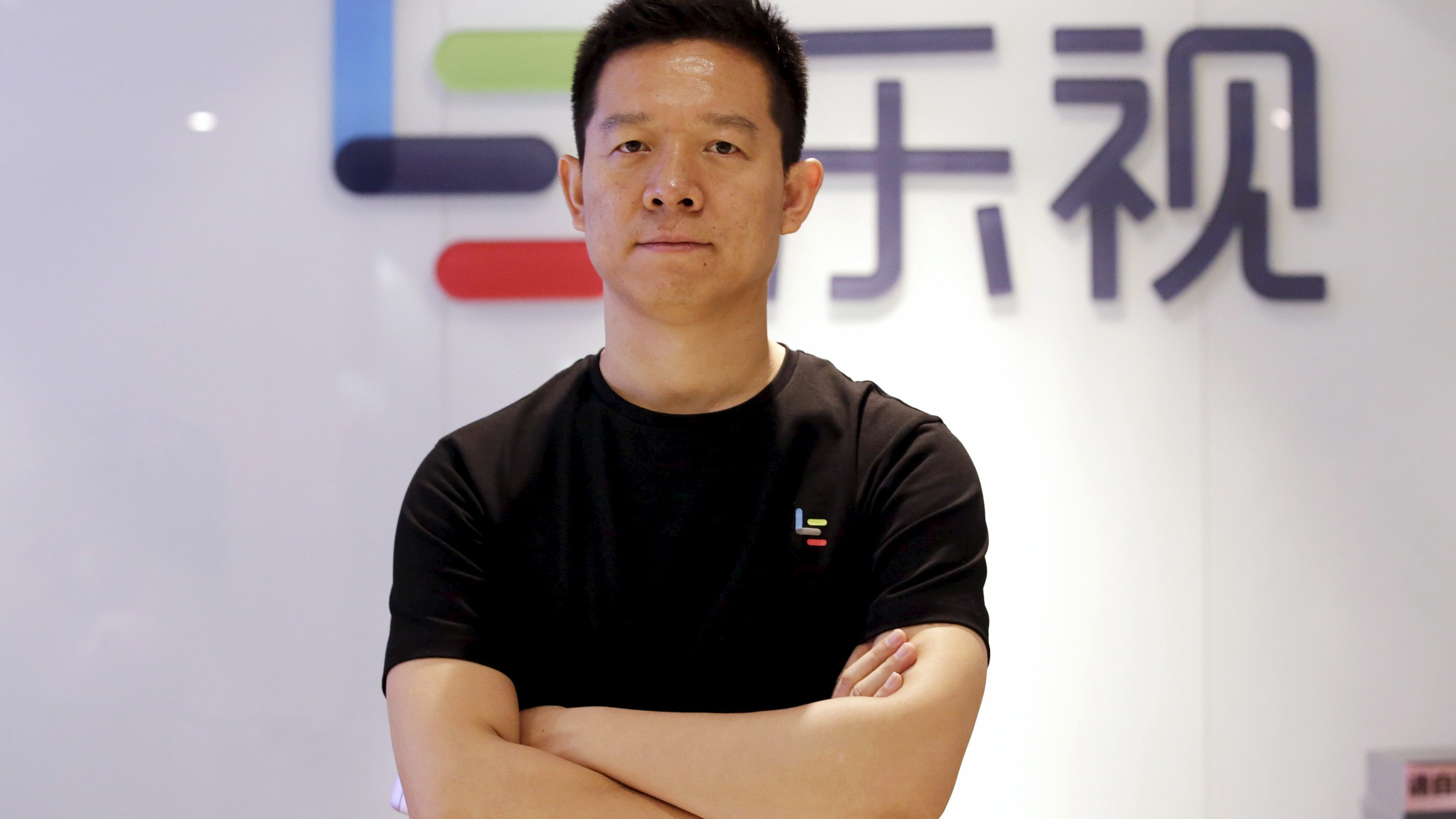 Jia Yueting, co-founder and head of Le Holdings Co Ltd, also known as LeEco and formerly as LeTV, poses for a photo in front of a logo of his company after a Reuters interview at LeEco headquarters in Beijing, China, picture taken April 22, 2016. To match Insight AUTOSHOW-BEIJING/CHINA-LEECO     REUTERS/Jason Lee - GF10000393670