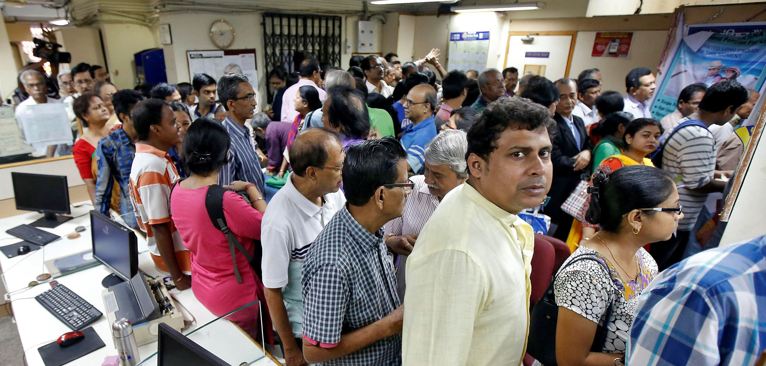People queue to withdraw and deposit their money inside a branch of Indian Bank in Kolkata, India, November 10, 2016.  - S1AEULYSXBAA
