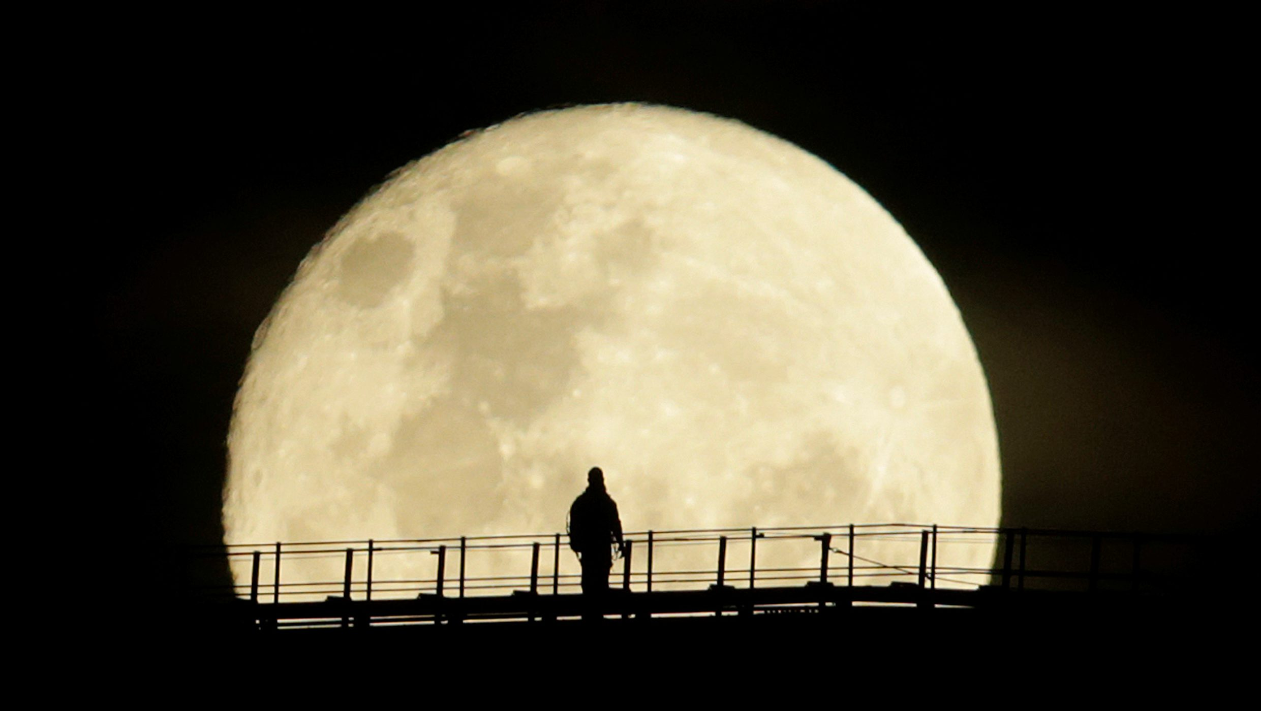 A man walks on the top span of the Sydney Harbour Bridge as the supermoon enters its final phase in Sydney, Australia, November 15, 2016.