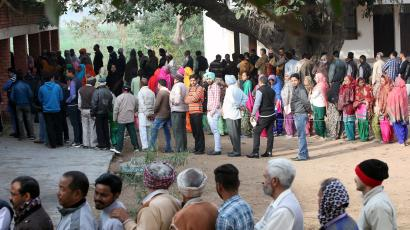 Voters line up to cast their votes outside a polling station during the state assembly election in the northern state of Punjab, in the village of Nada