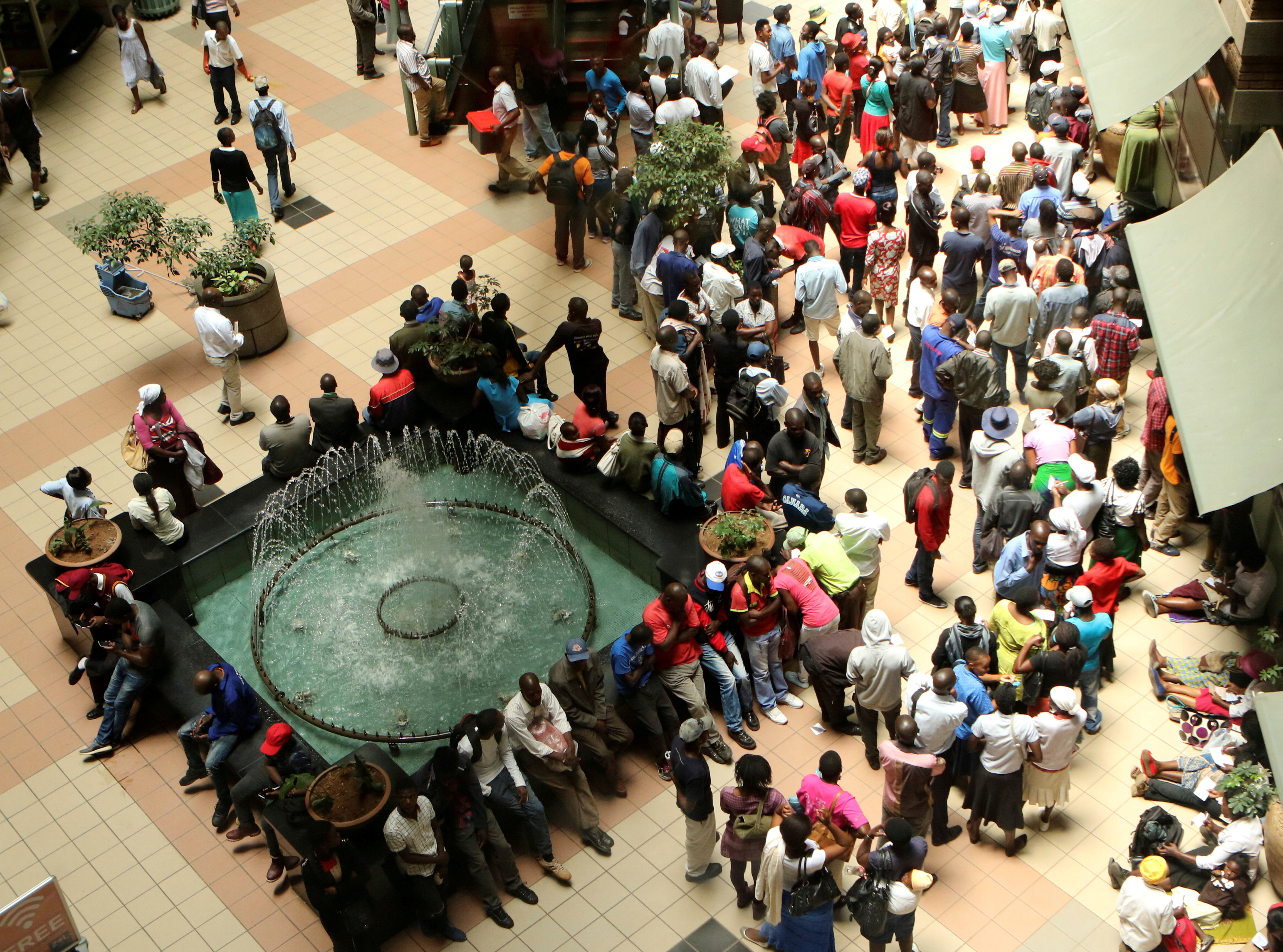 People queue to withdraw money from a bank in Harare, Zimbabwe's capital, March 8, 2017.