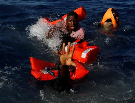Migrants try to stay afloat after falling off their rubber dinghy during a rescue operation by the Malta-based NGO Migrant Offshore Aid Station (MOAS) ship in the central Mediterranean in international waters some 15 nautical miles off the coast of Zawiya in Libya, April 14, 2017. All 134 sub-Saharan migrants survived and were rescued by MOAS.