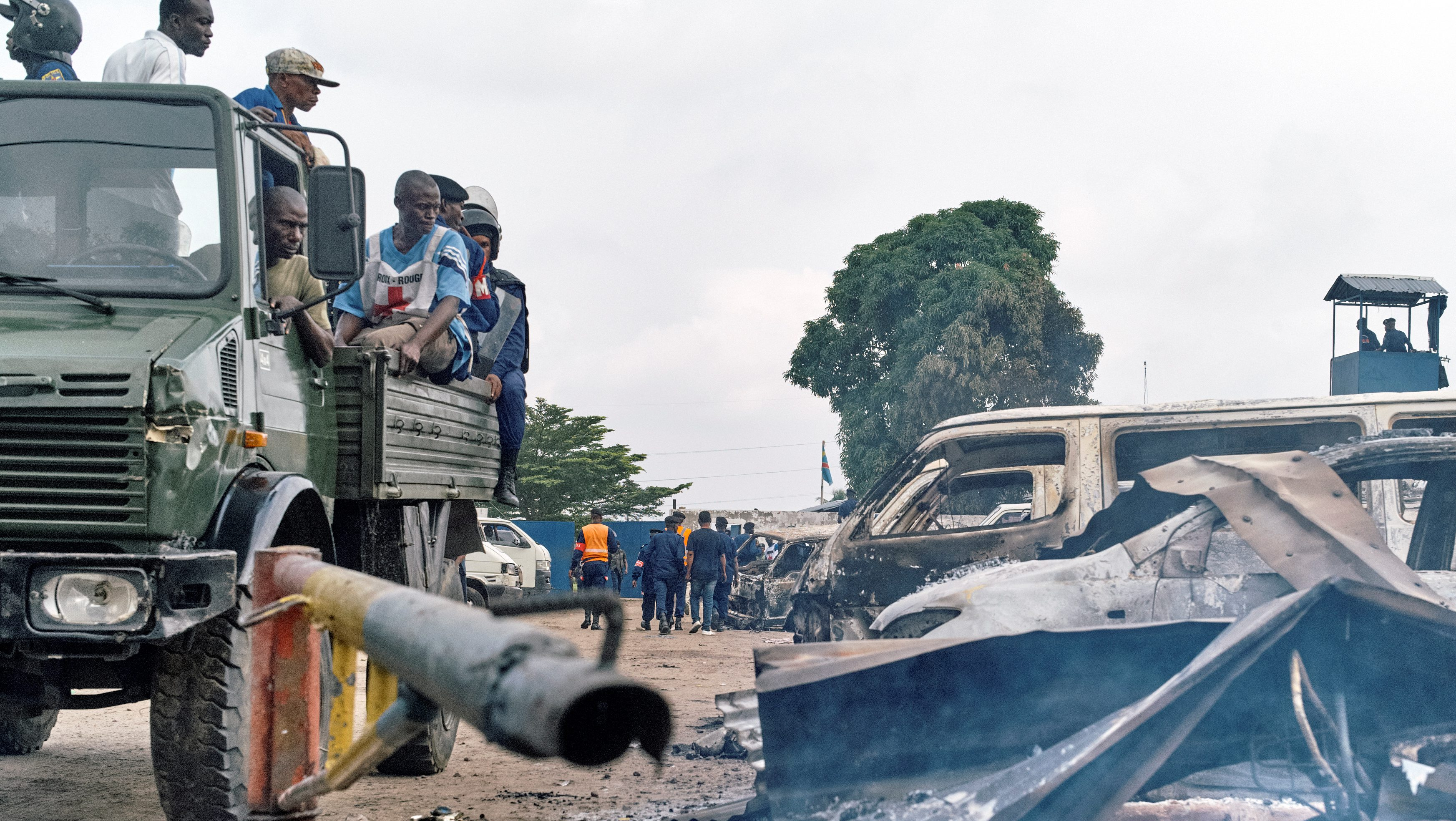 Security personnel sitting on a truck watch burned vehicles at the front gate of the Makala prison in Kinshasa