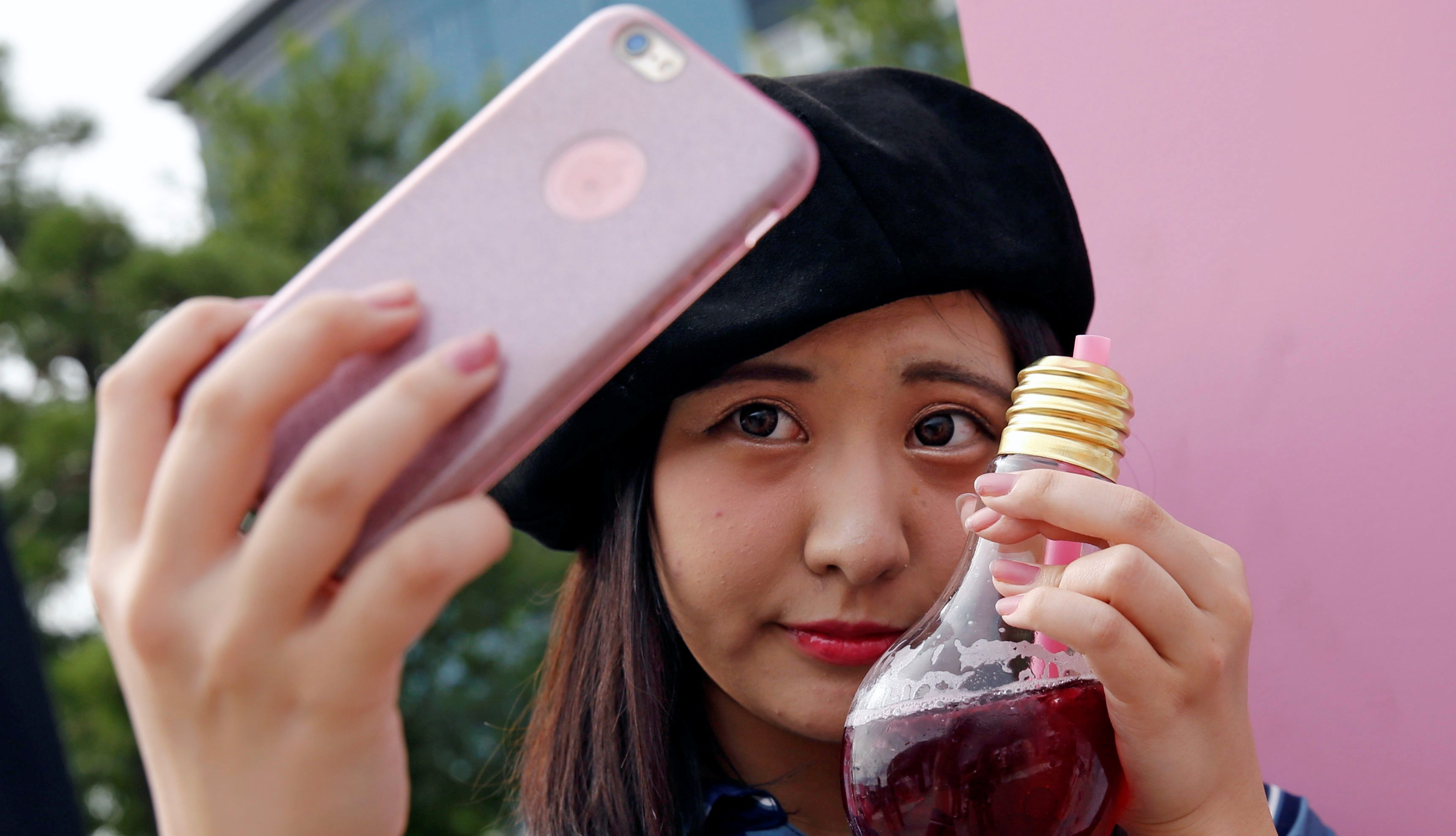 A woman takes a selfie with a drink from FOOD BOAT cafe during the Photogenic Sweets Festa at a shopping mall in Tokyo