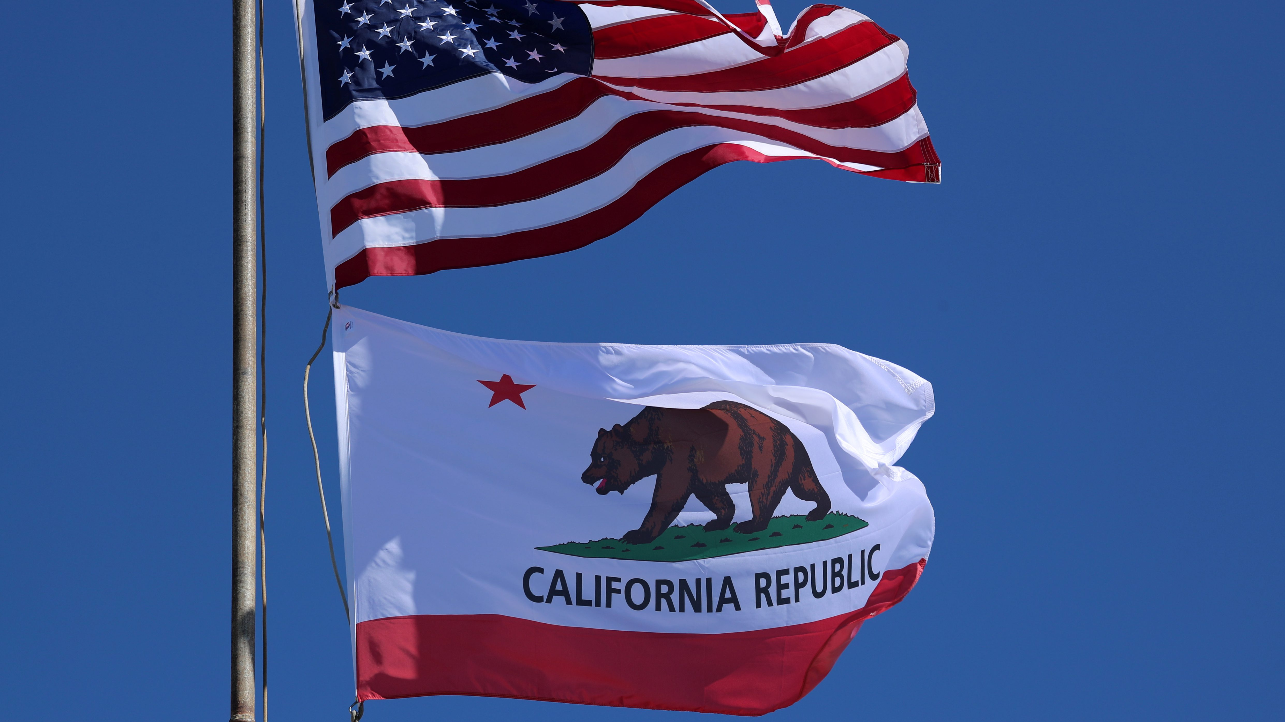 U.S. and California flags fly together on a flag pole in Oceanside, California, U.S., October 24,  2017.     REUTERS/Mike Blake - RC1292F3C1C0