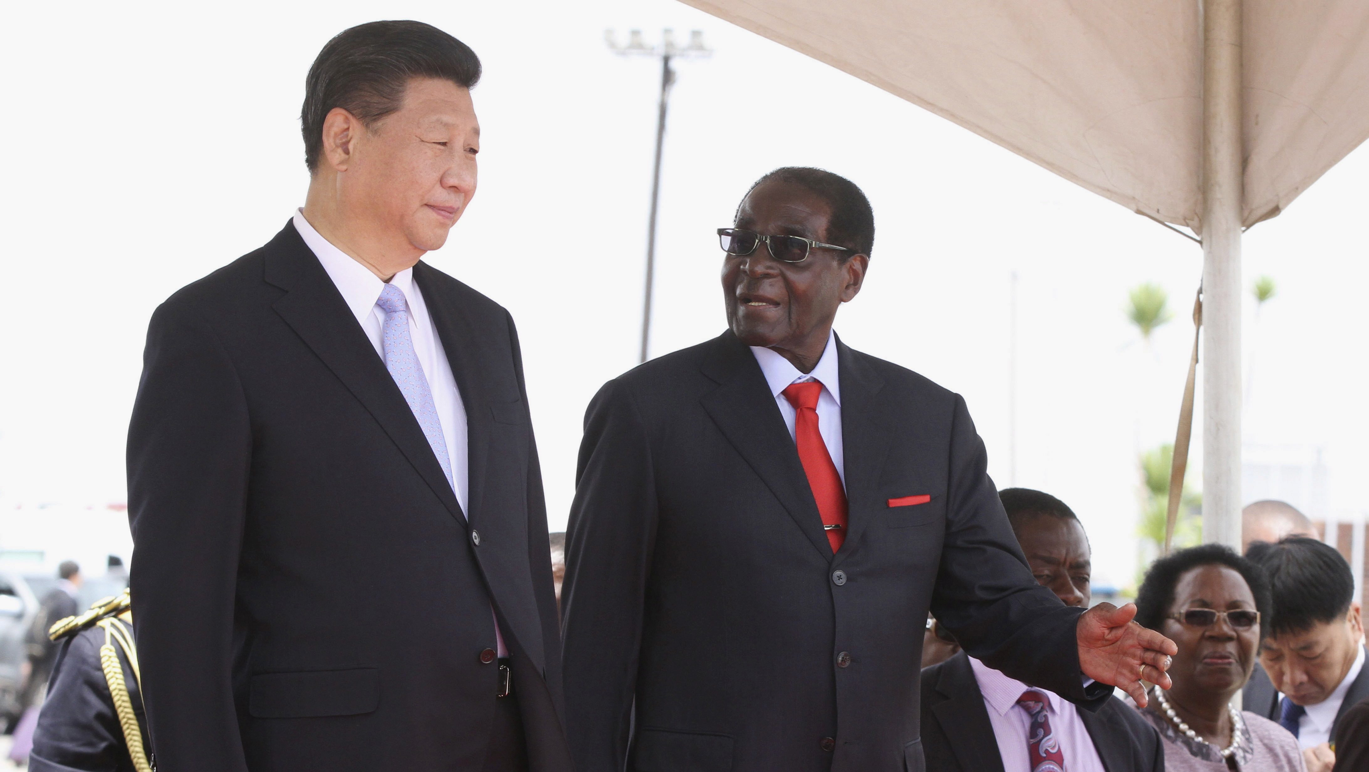 Chinese President Xi Jinping talks with Zimbabwean President Robert Mugabe on arrival for a state visit in Harare, Zimbabwe December 1, 2015.