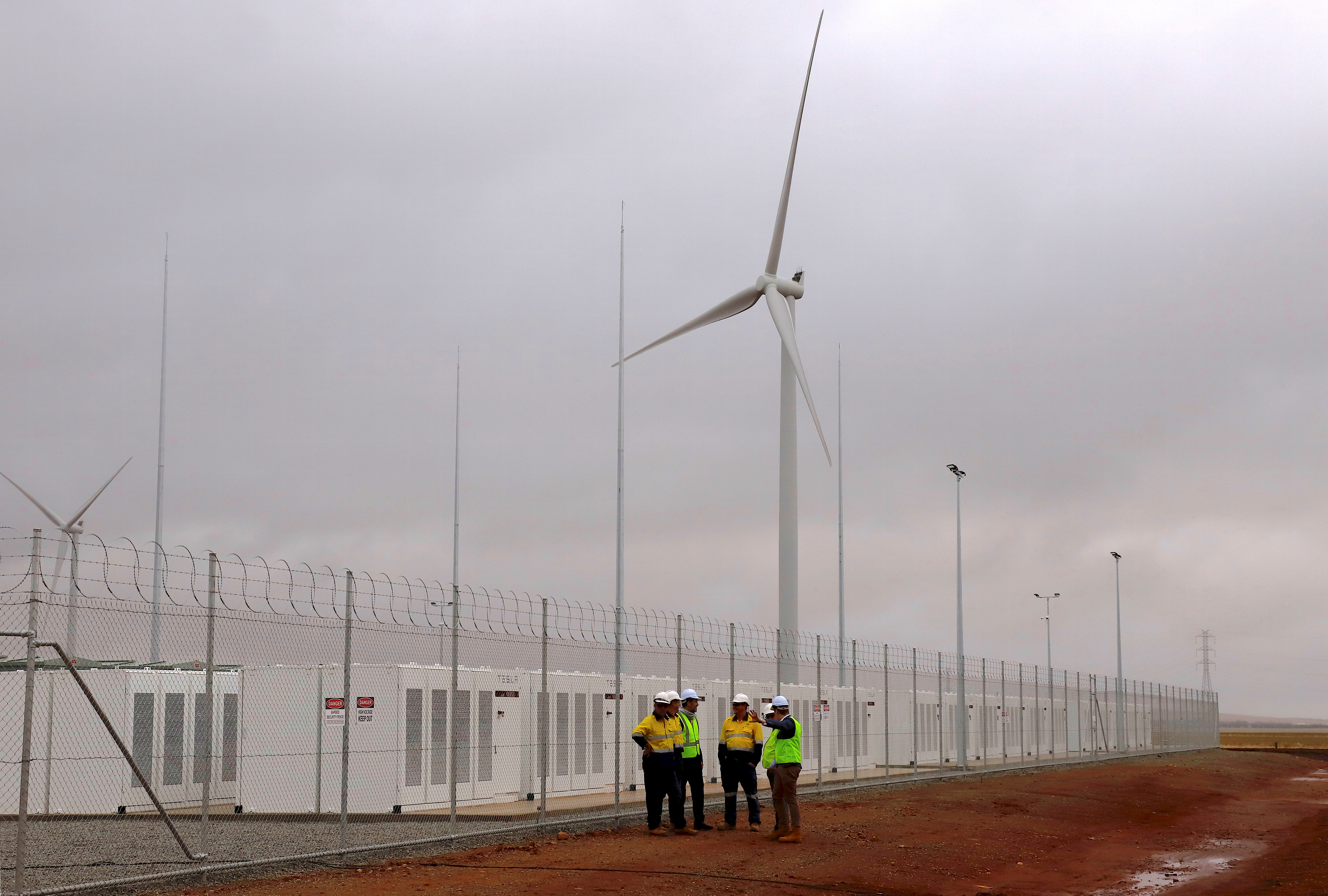 Officials and workers gather outside the compound housing the Hornsdale Power Reserve, featuring the world's largest lithium ion battery made by Tesla, during the official launch near the South Australian town of Jamestown, in Australia, December 1, 2017. REUTERS/David Gray - RC1D99DC5C00