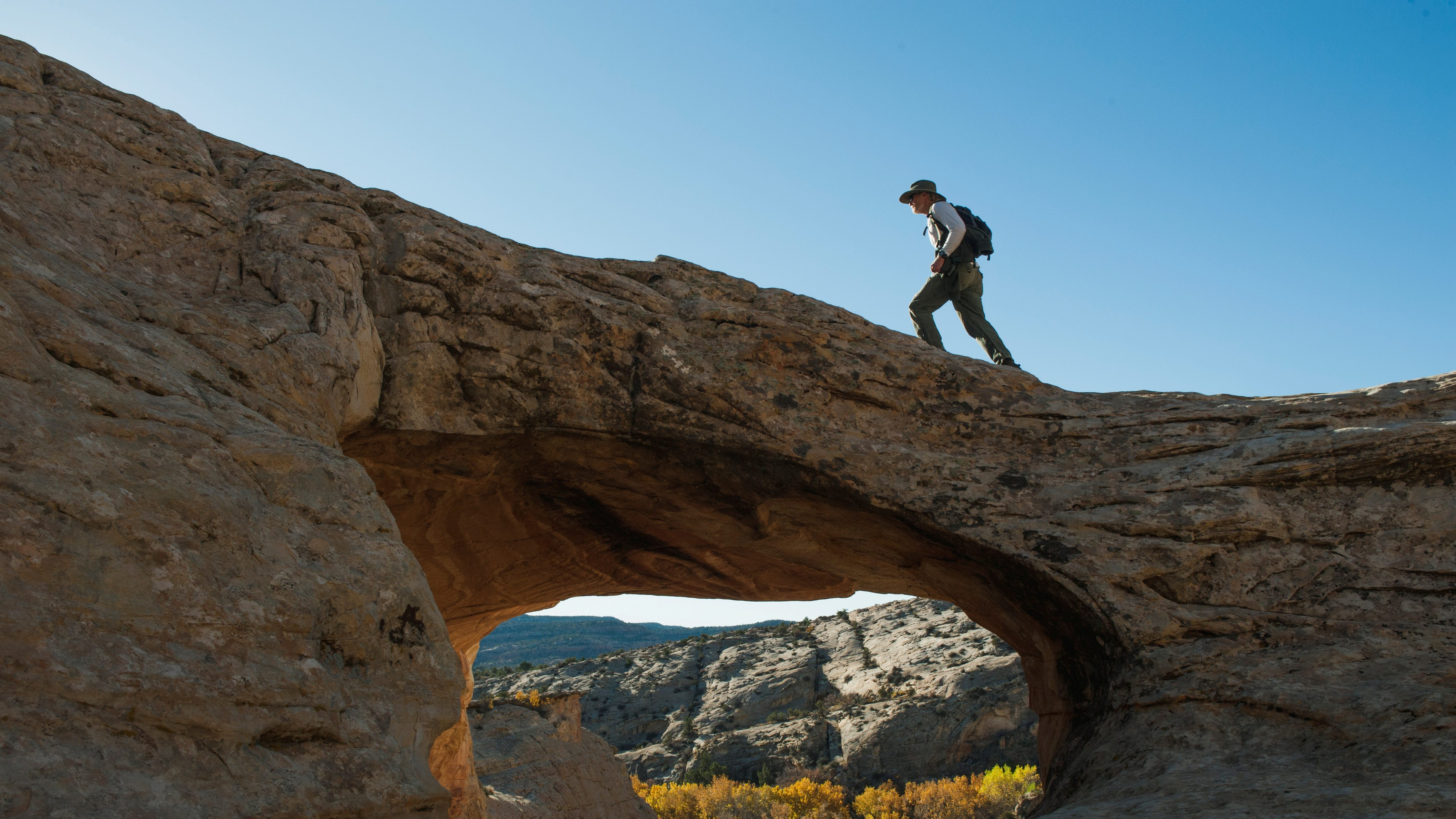 FILE PHOTO: A man walks over a natural bridge at Butler Wash in Bears Ears National Monument near Blanding