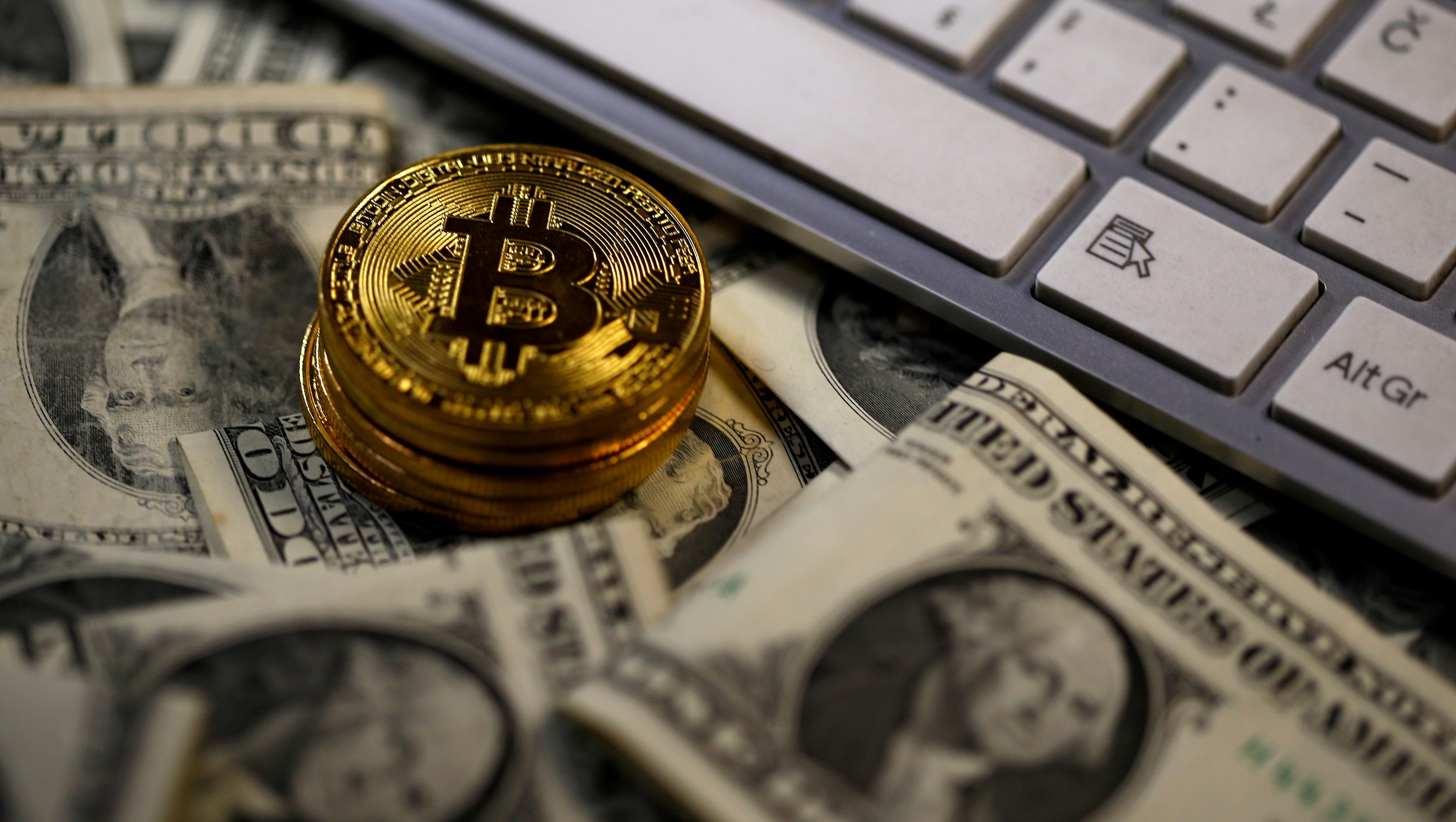 FILE PHOTO:   Bitcoin (virtual currency) coins placed on Dollar banknotes, next to computer keyboard, are seen in this illustration picture, November 6, 2017.  REUTERS/Dado Ruvic/Illustration/File Photo - RC1EF9D6BE50