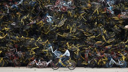 A worker rides a shared bicycle past piled-up shared bikes at a vacant lot in Xiamen, Fujian province, China December 13, 2017. Picture taken December 13, 2017. REUTERS/Stringer ATTENTION EDITORS - THIS IMAGE WAS PROVIDED BY A THIRD PARTY. CHINA OUT. - RC1C376F7180