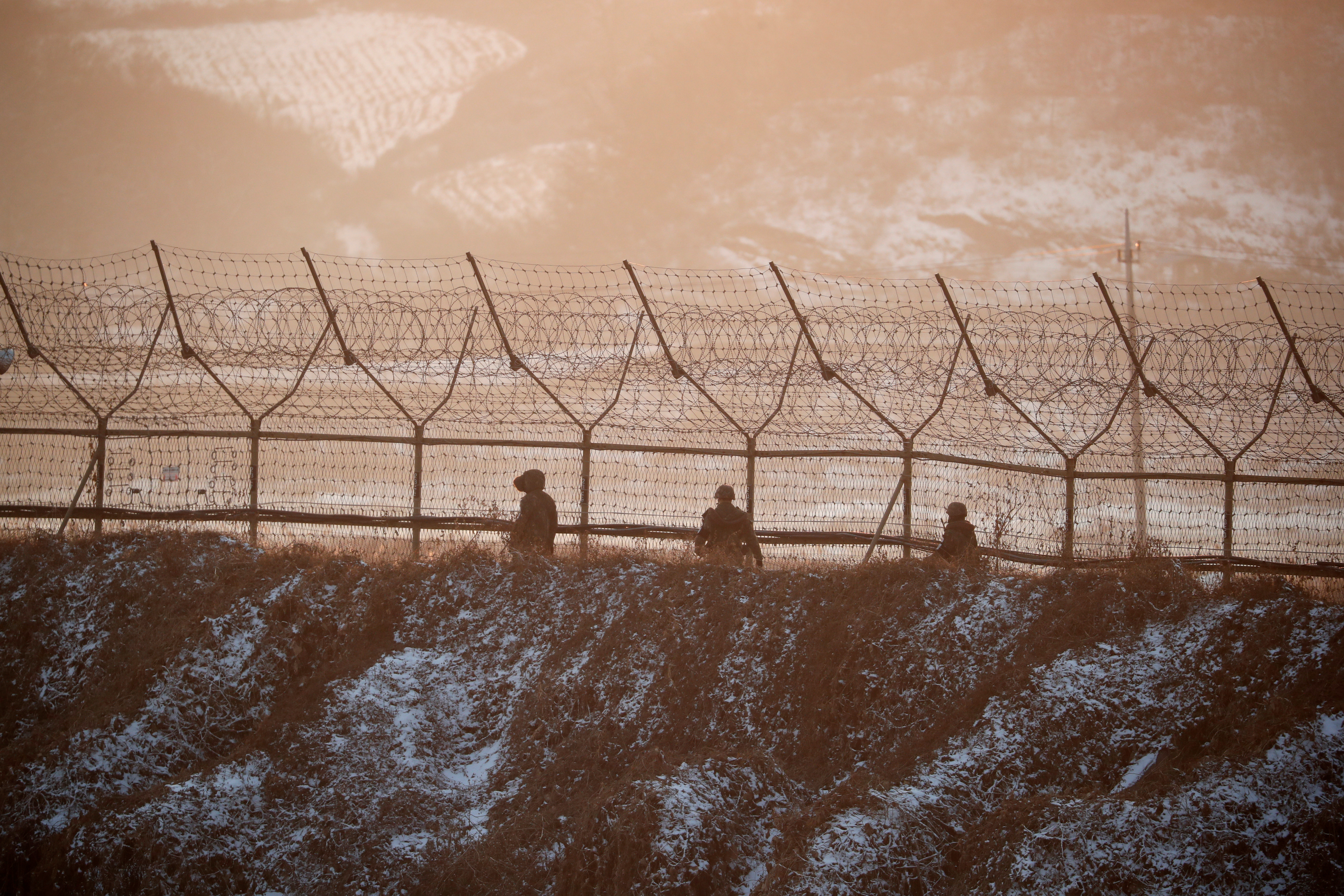 South Korean soldiers patrol along a barbed-wire fence near the demilitarized zone separating the two Koreas, in Paju, South Korea, December 21, 2017.