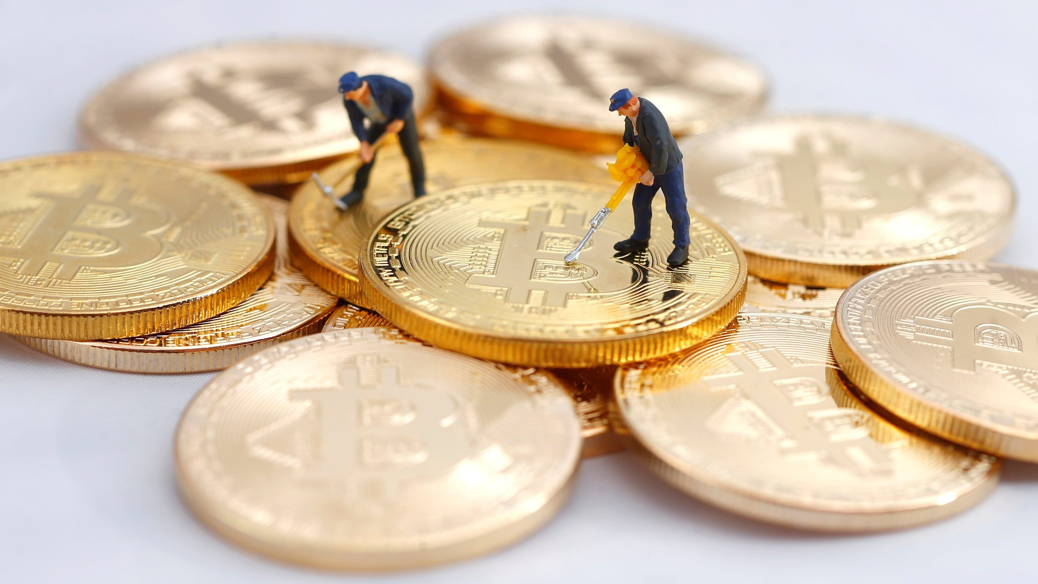 Small toy figures are seen on representations of the Bitcoin virtual currency in this illustration picture, December 26, 2017.