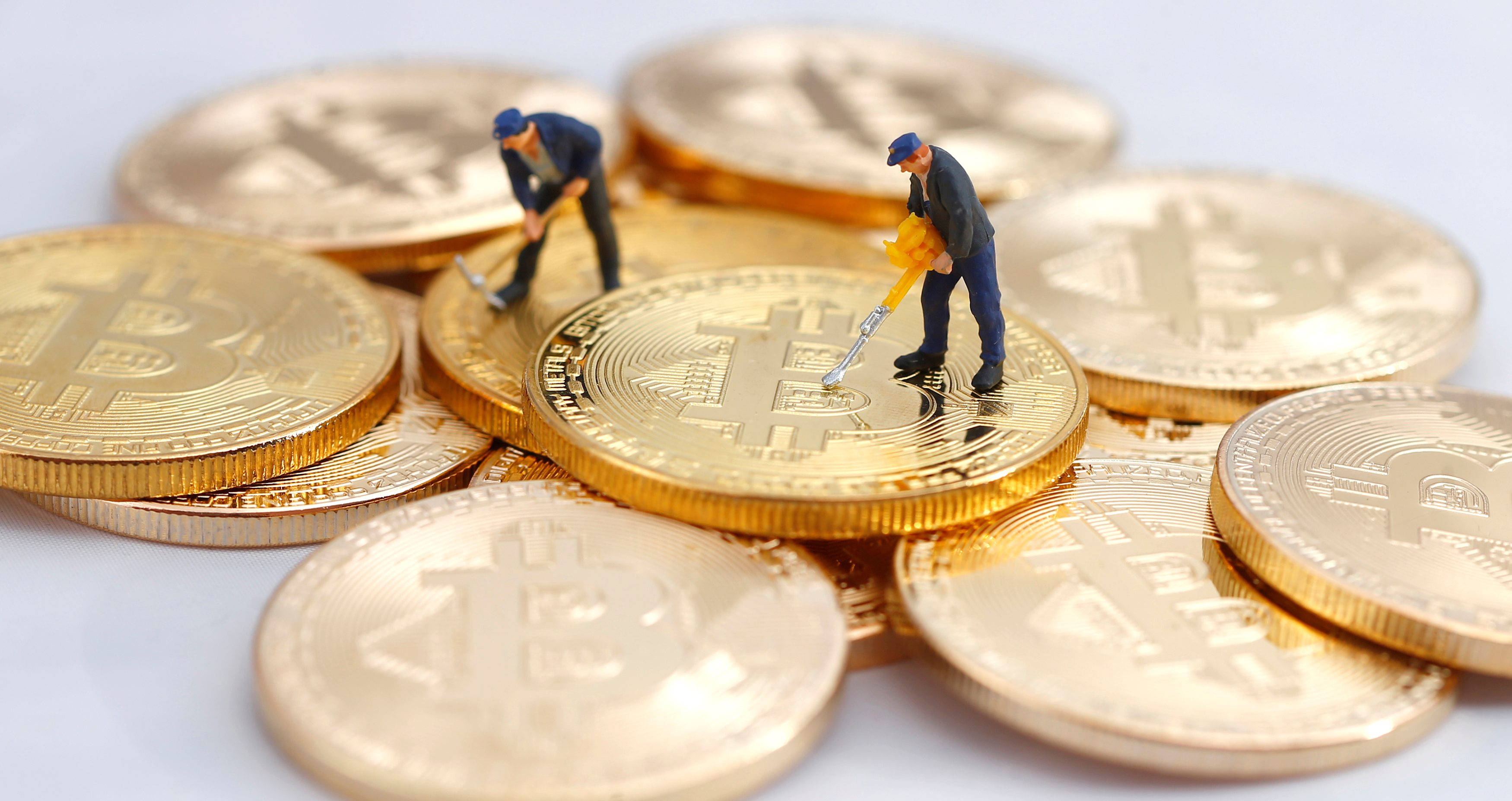 Small toy figures are seen on representations of the Bitcoin virtual currency in this illustration picture