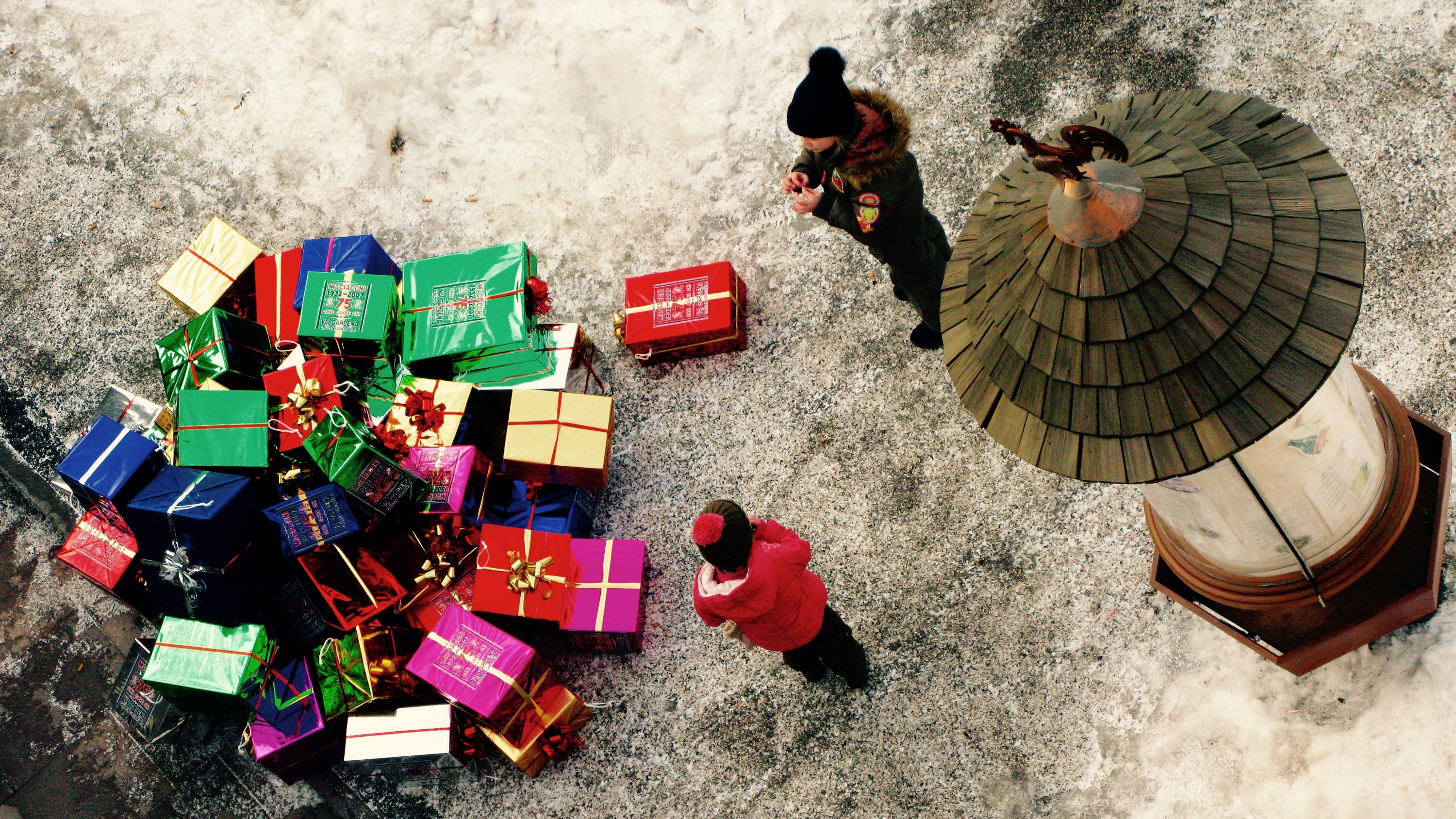 Presents piled on the ground with onlooking children.